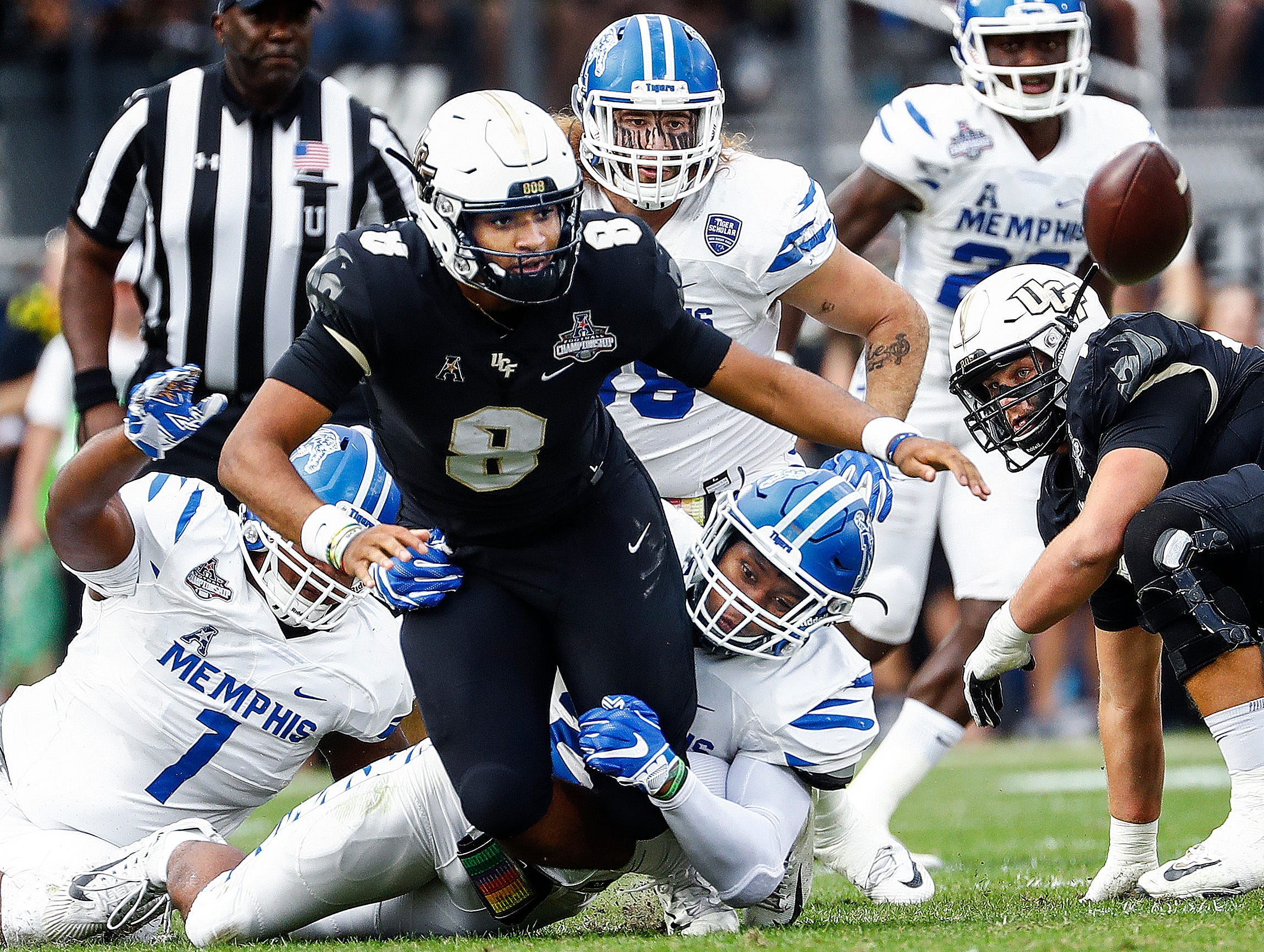 The Memphis defense causes UCF quarterback Darriel Mack Jr. (middle) to fumble during action at the AAC Championship Football game Saturday, December 1, 2018 in Orlando. Memphis recovered the ball on the play.
