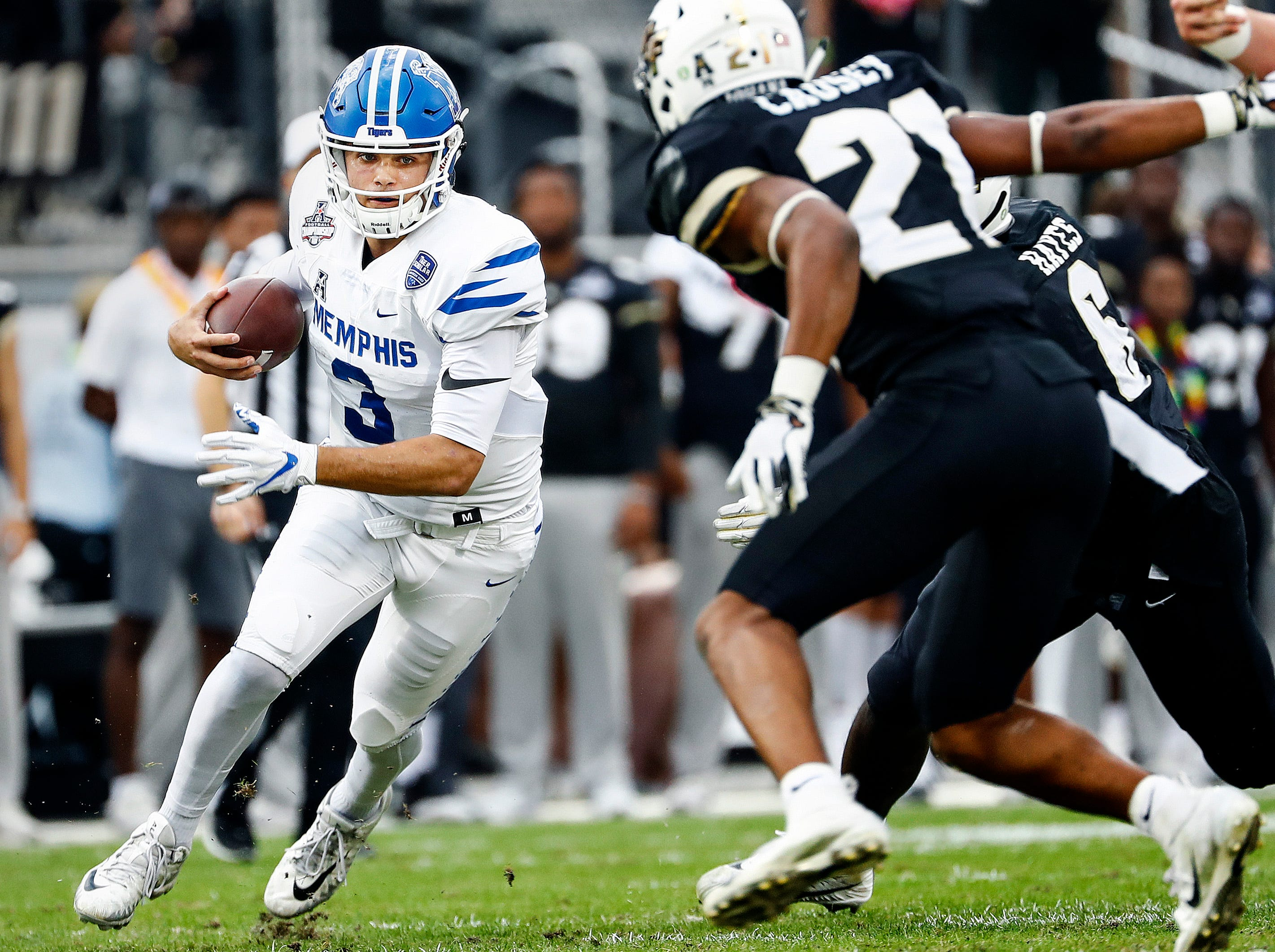 Memphis quarterback Brady White (left) looks for a lane against the UCF defense during action at the AAC Championship Football game Saturday, December 1, 2018 in Orlando.