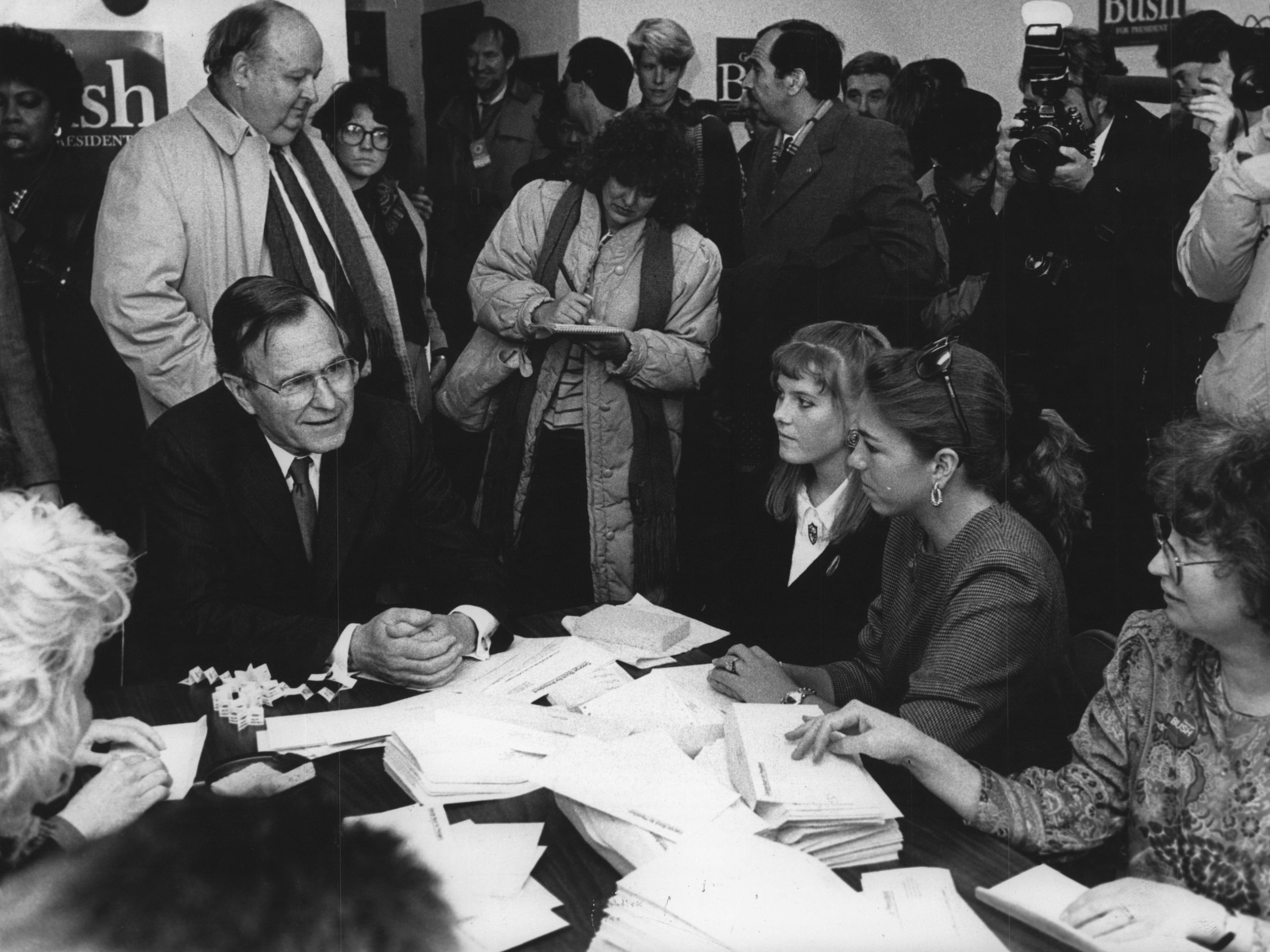 Vice President George Bush is surrounded by members of the media as he spoke with campaign workers in 1988 at his Milwaukee campaign headquarters.