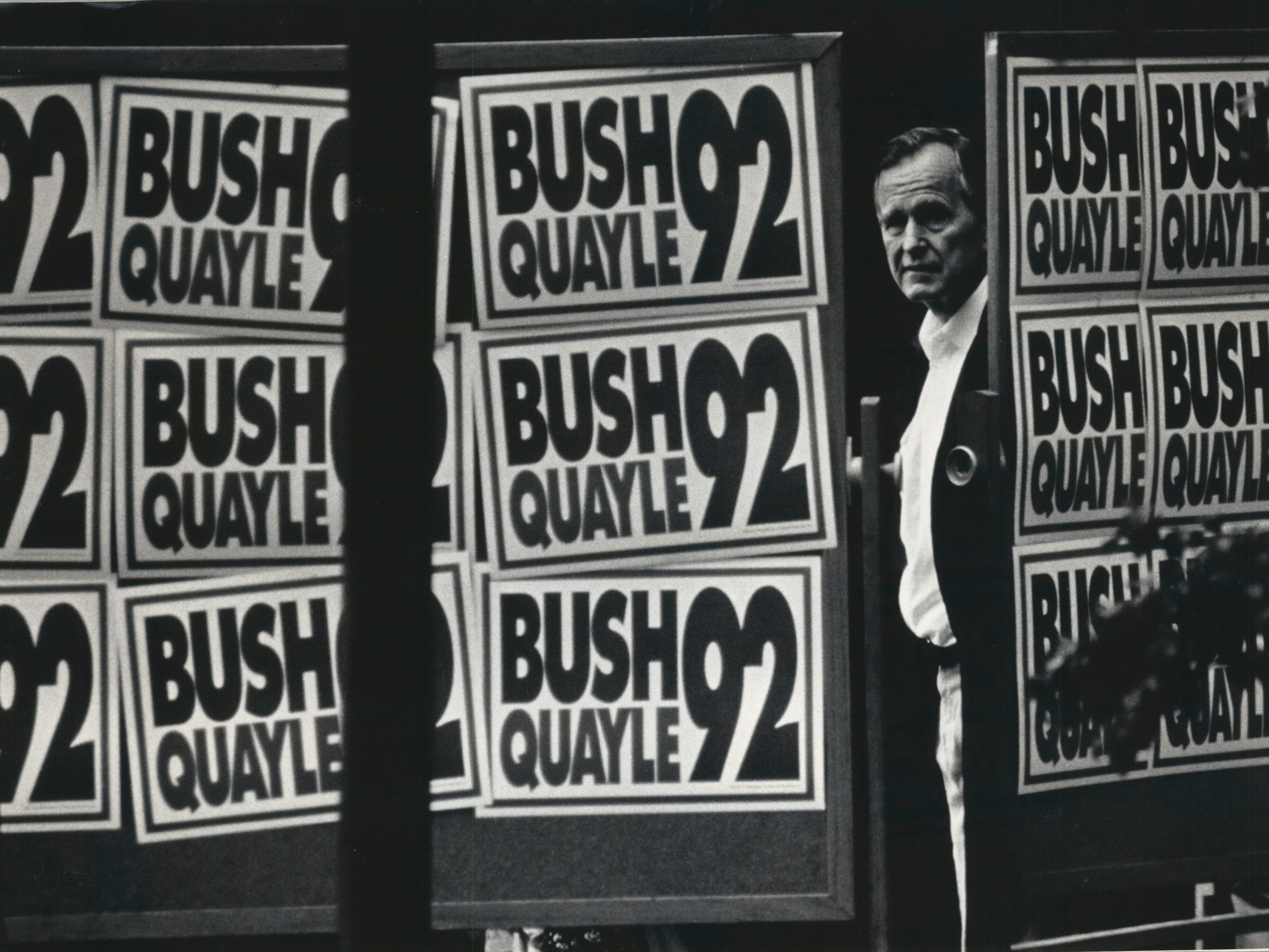 President Bush peers out at the Waukesha County Exposition Center crowd from behind a screen plastered with campaign posters in 1992 before being introduced by U.S Sen. Bob Kasten.