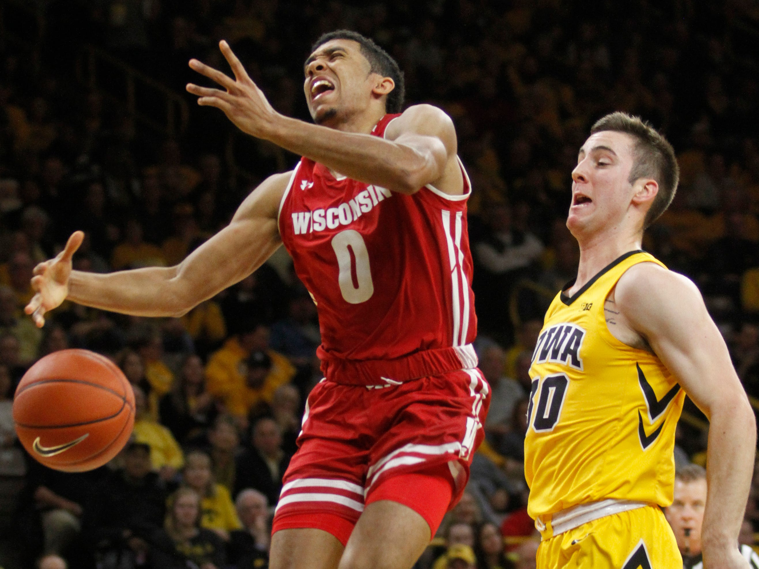 UW  guard D'Mitrik Trice is fouled in the first half by Iowa guard Connor McCaffery on Friday night.