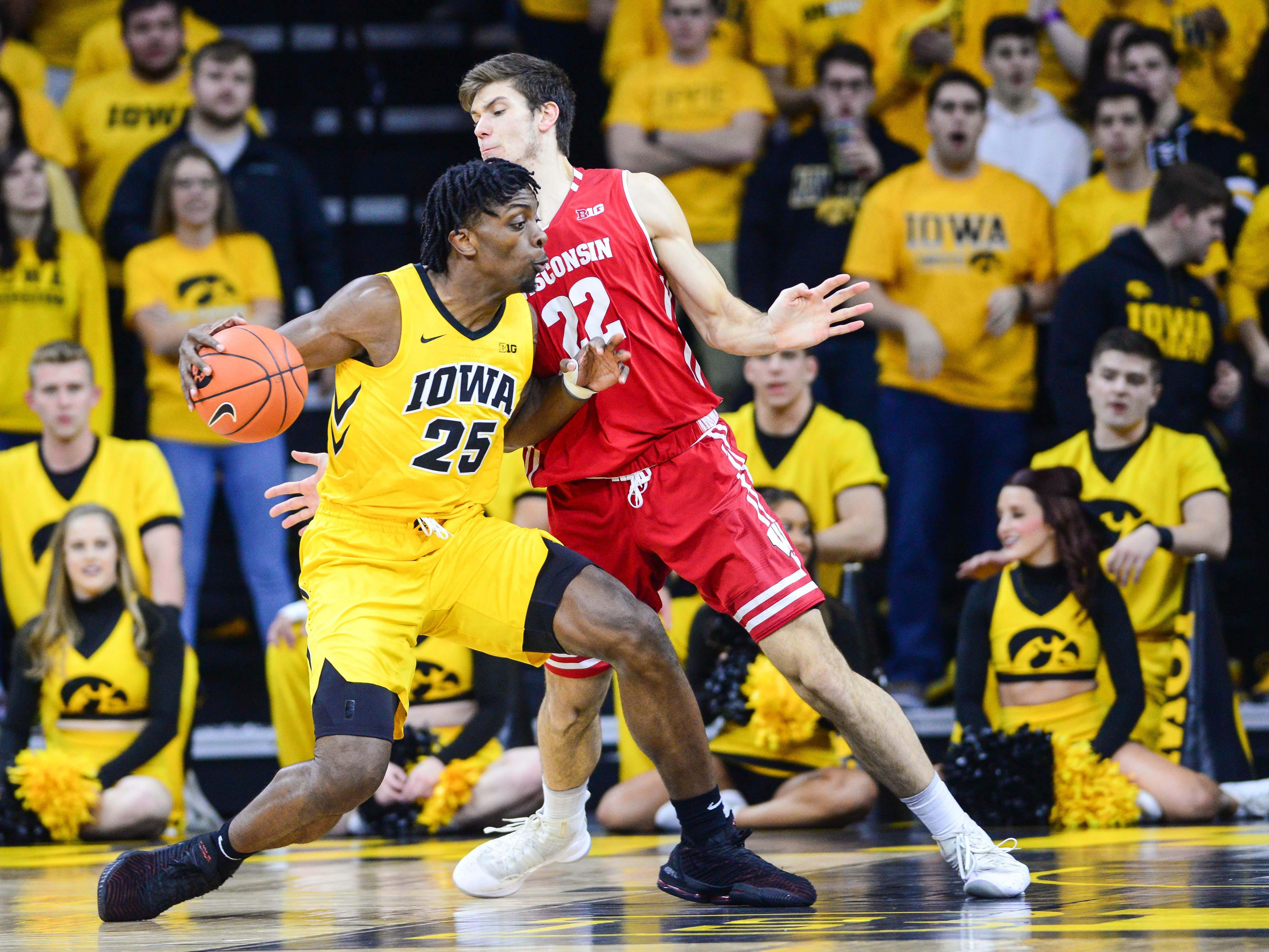 Badgers forward Ethan Happ bodies up on Tyler Cook as he tries to prevent the Iowa forward from getting to the basket on Friday night.