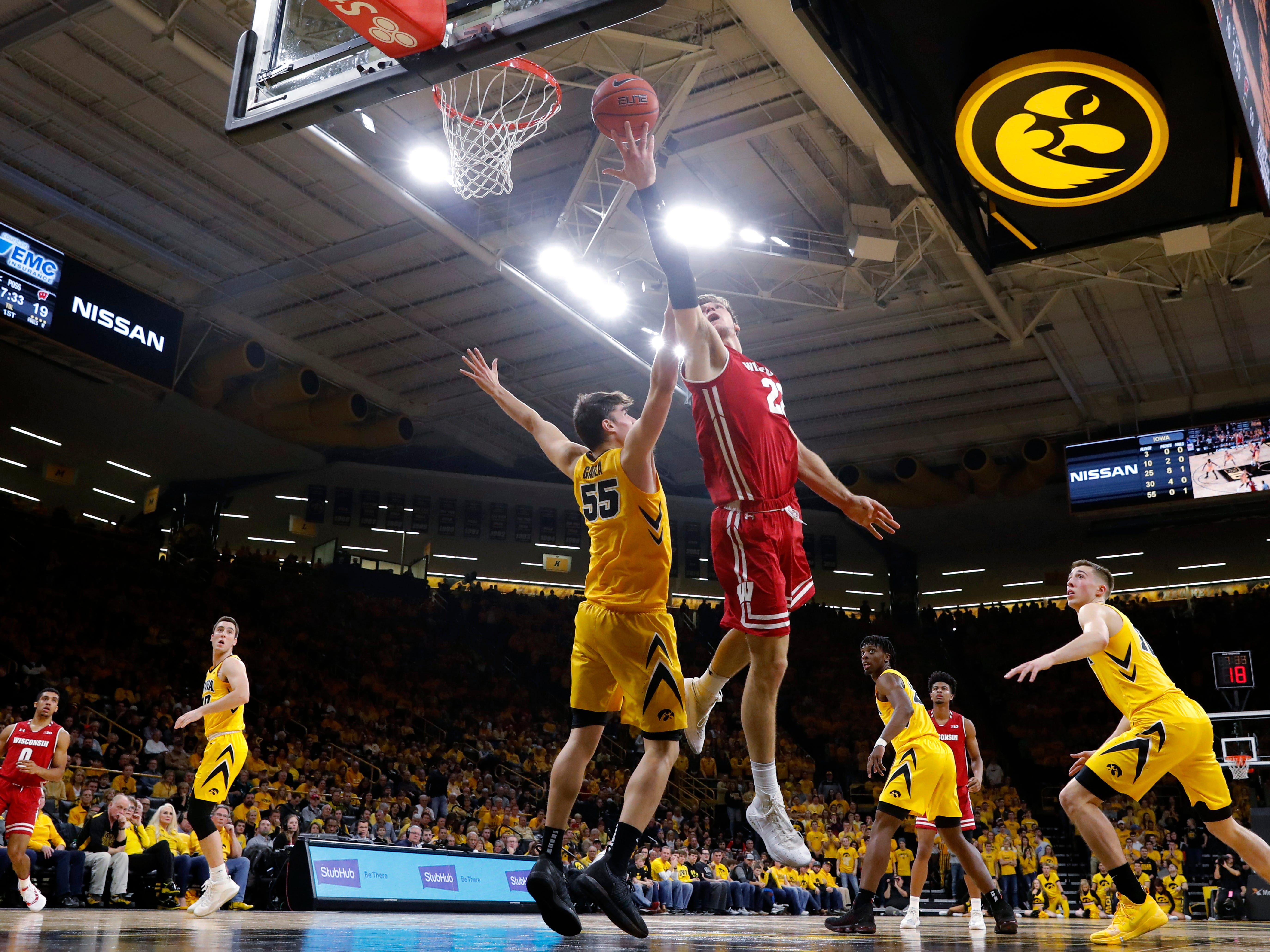Wisconsin forward Ethan Happ goes up for a underhanded lay in against Iowa forward Luka Garza during the first half Friday night.