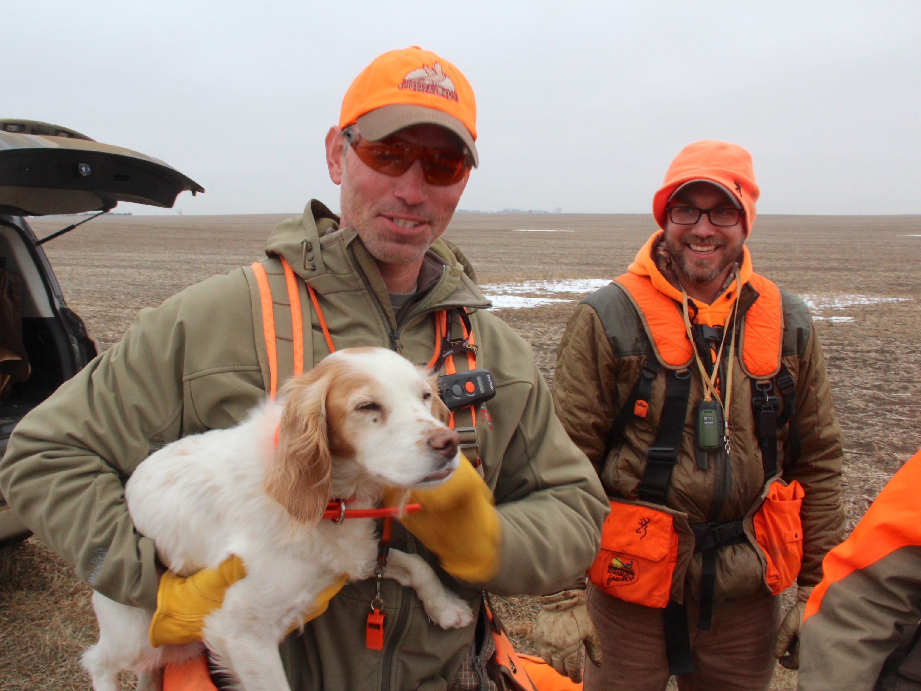 Eric Johannsen of Aberdeen, South Dakota holds an English cocker spaniel owned by Anthony Hauck, right, of Prior Lake, Minnesota, prior to a pheasant hunt on the farm owned by Johannsen's family.