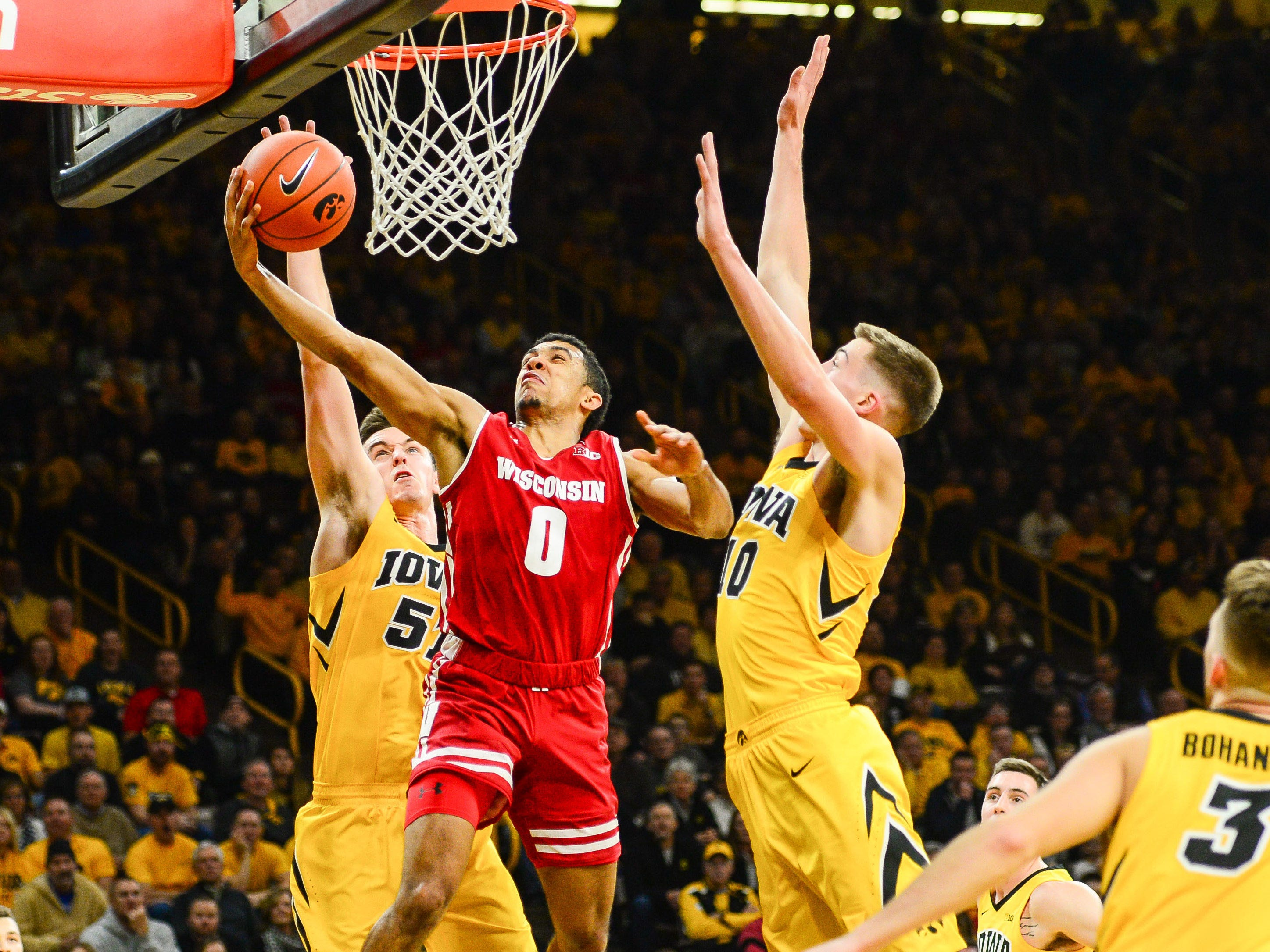 UW guard D'Mitrik Trice goes in for a layup between Iowa's Nicholas Baer (left) and Joe Wieskamp during the second half on Friday night.