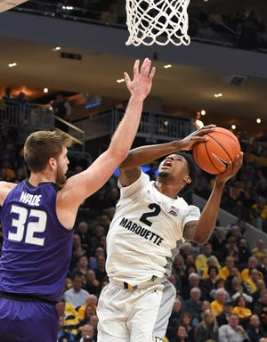 Marquette guard/forward Sacar Anim goes up for a shot under the basket while being guarded by Kansas State forward Dean Wade on Saturday.