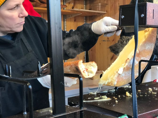 Melted raclette cheese is scraped onto a crunchy baguette at the Baked Cheese Haus at the Christkindlmarket in Milwaukee.
