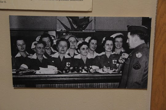 A U.S. soldier poses for a photograph with servers at the Aberdeen Pheasant Canteen during World War II.