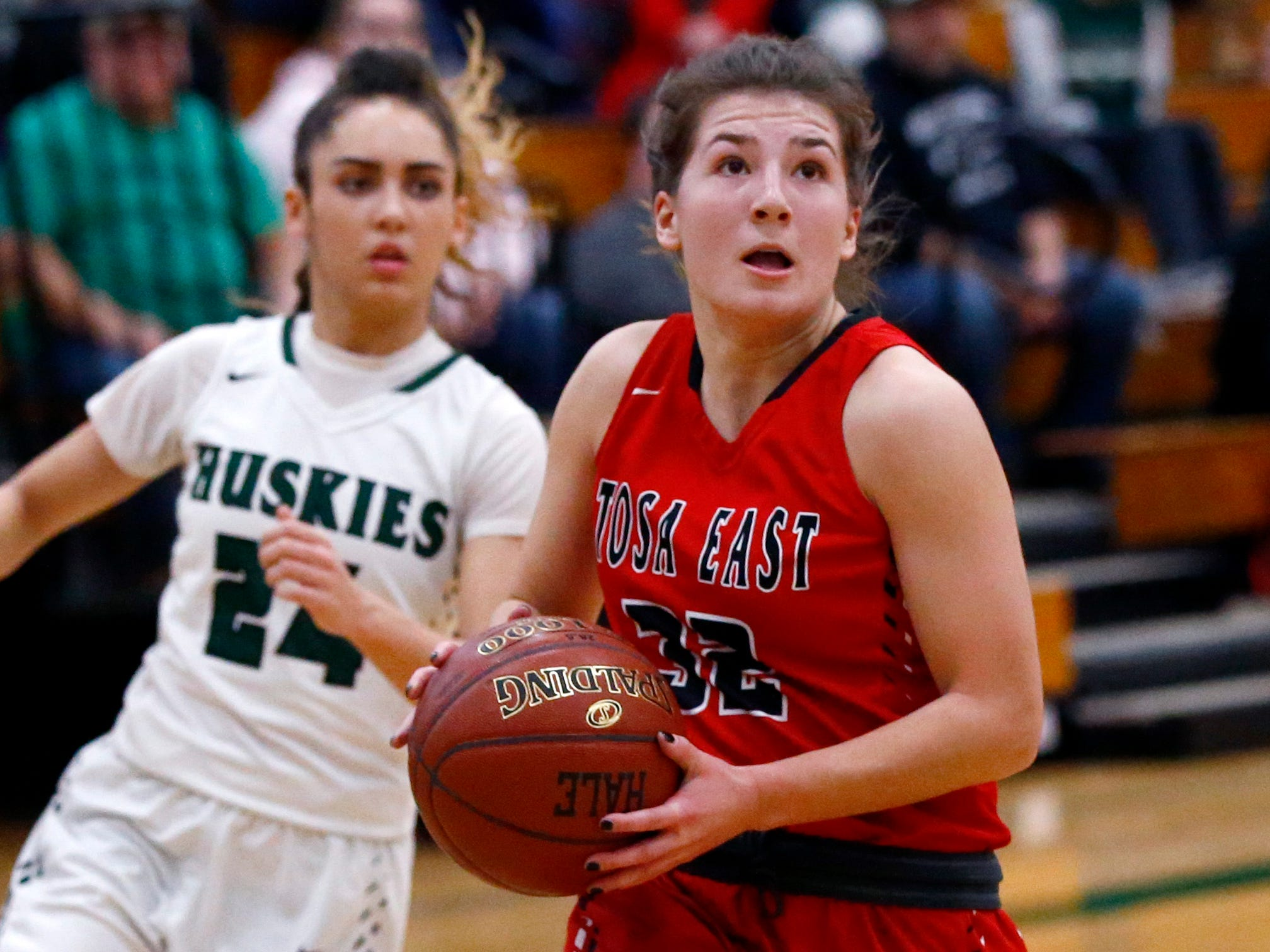 Wauwatosa East's Sydney Halstead drives past West Allis Hale's Natalia Leguizamon for two points at Hale on Nov. 30.