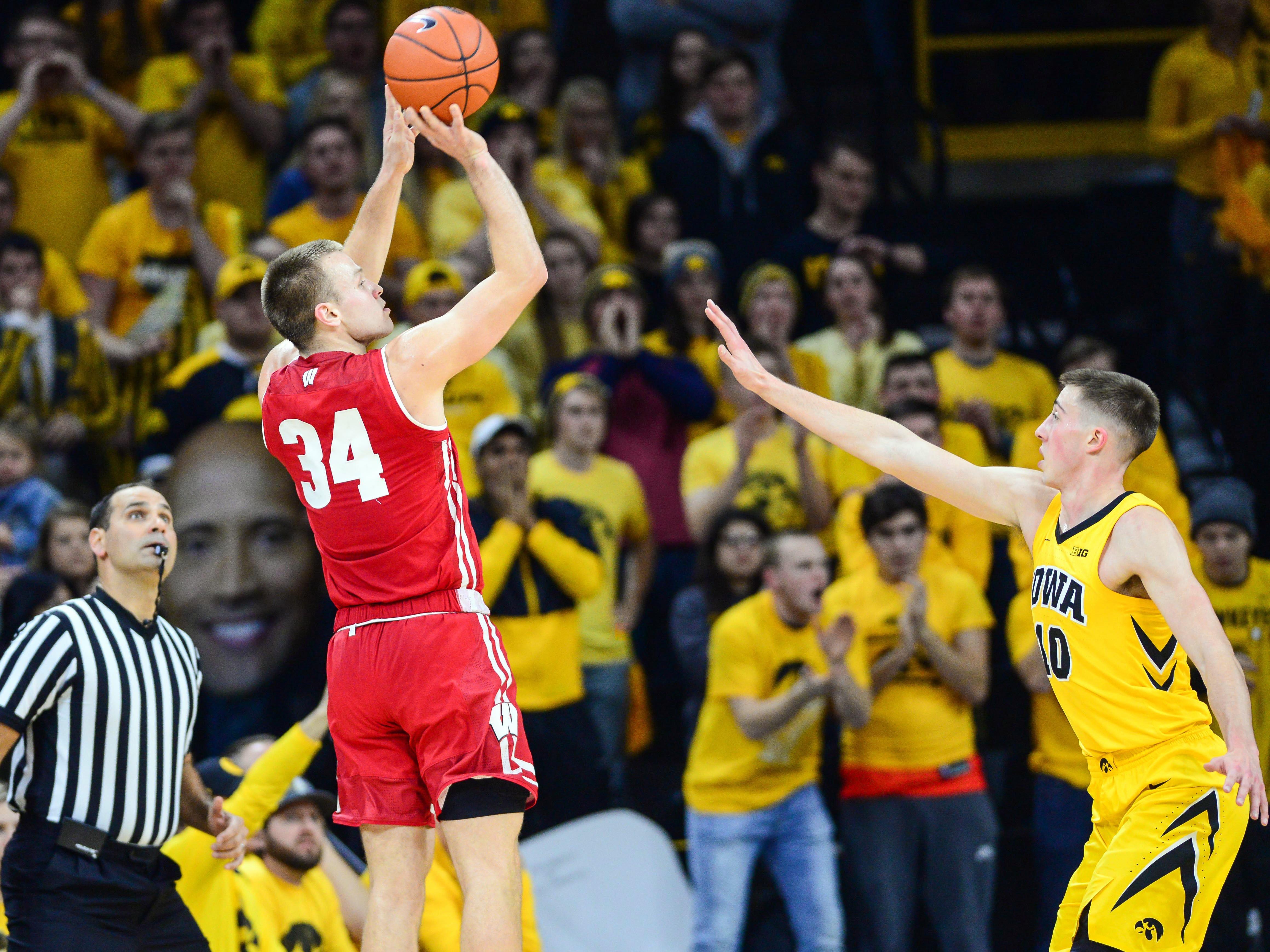 Badgers guard Brad Davison hoists up a three-pointer over Iowa guard Joe Wieskamp on Friday night.