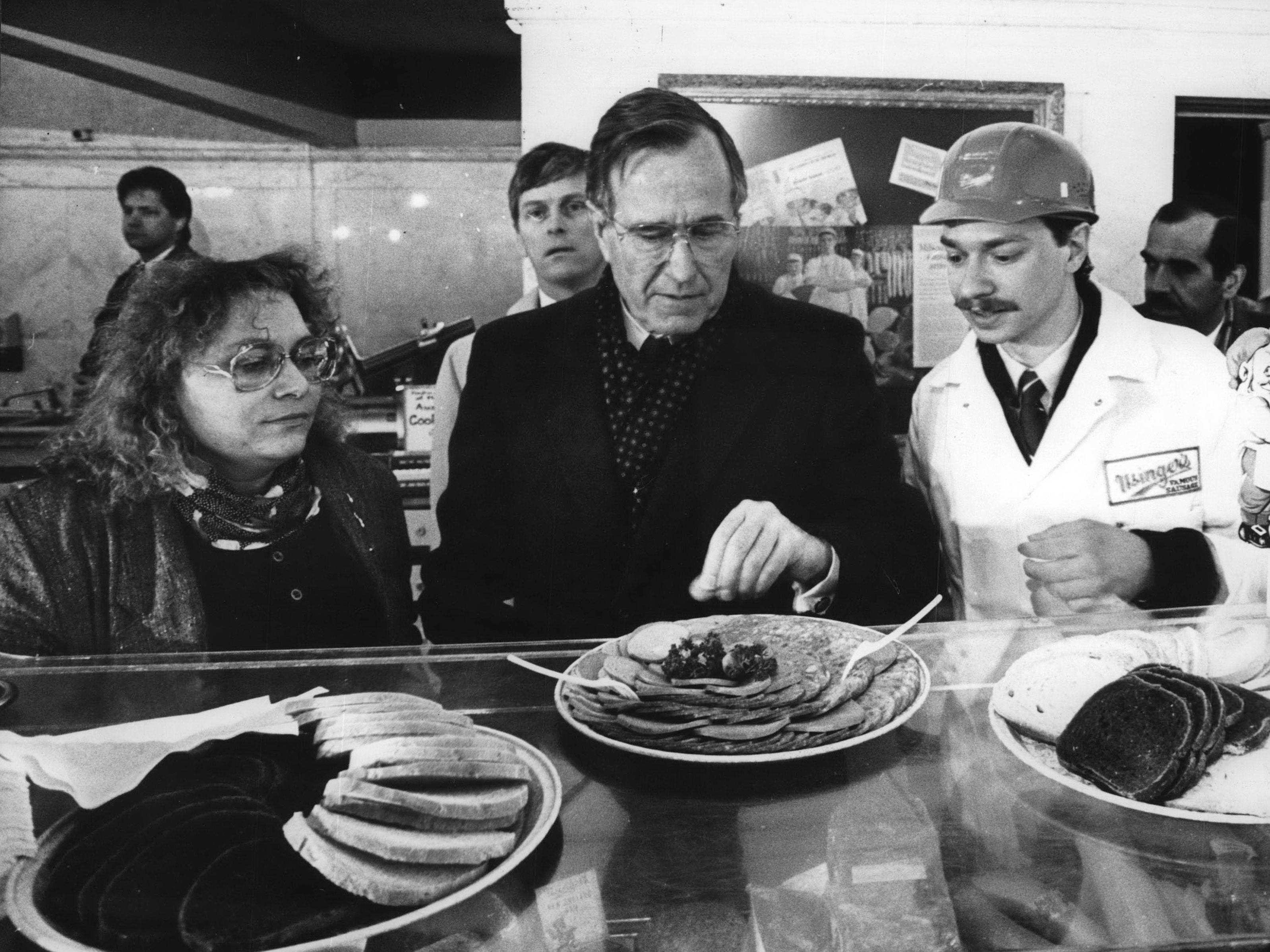 Debra Usinger (left), Vice President George Bush and Fritz Usinger, fourth-generation wurstmacher at Usinger Famous Sausage, samples the company's products during a campaign swing through Milwaukee in 1988. Bush, a candidate for the Republican Party nomination for president, also spoke to students at Marquette University High School.