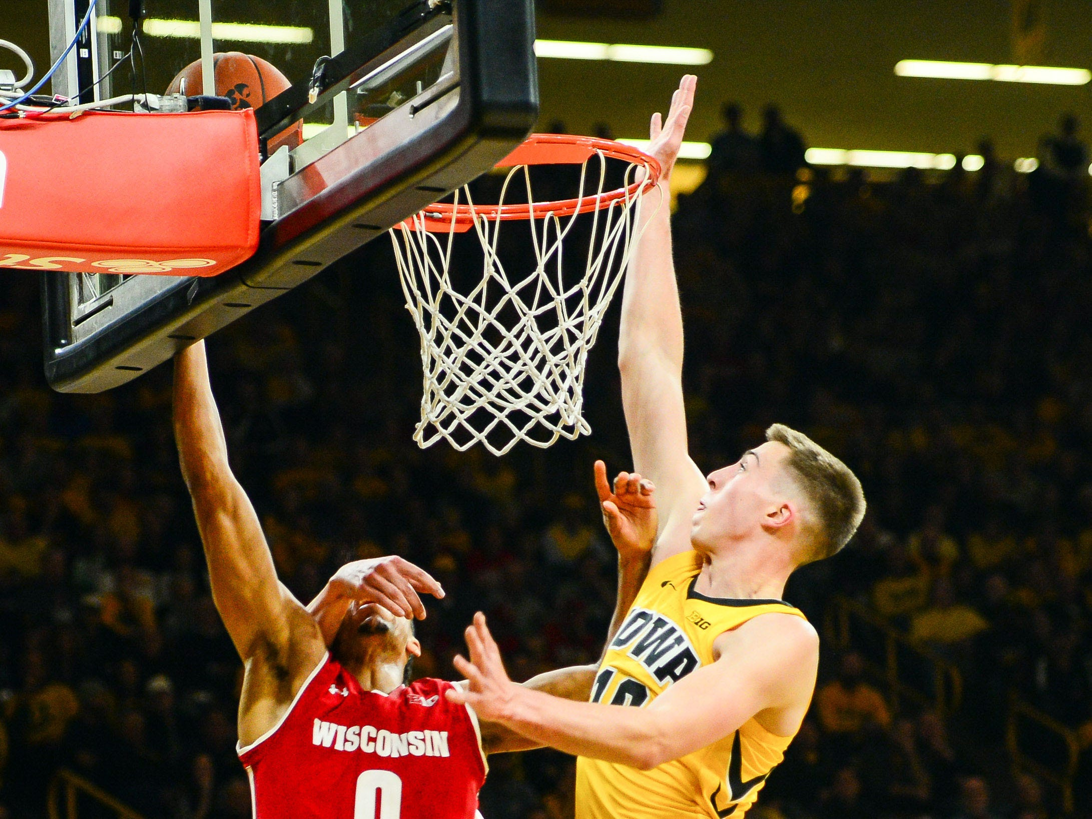 Badgers guard D'Mitrik Trice gets whacked on the side of the face by Iowa's Nicholas Baer as he goes up for a layup during the second half on Friday night at Carver-Hawkeye Arena in Iowa City.