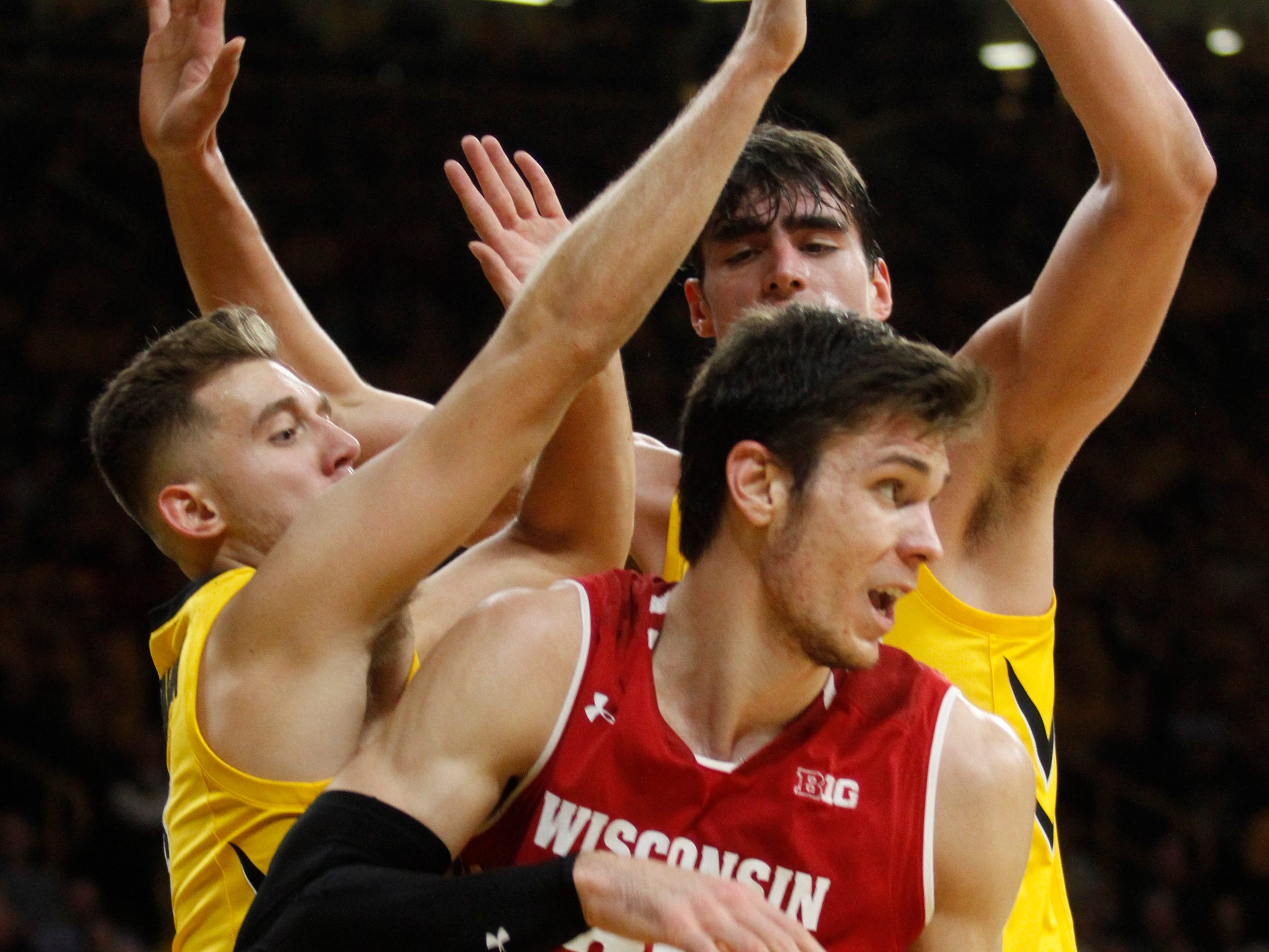 Wisconsin forward Ethan Happ looks for a teammate to dish off to as he's double-teamed by Iowa's Jordan Bohannon (left)  and Luka Garza on Friday night.