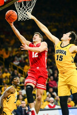 Nov 30, 2018; Iowa City, IA, USA; Wisconsin Badgers guard Trevor Anderson (12) goes to the basket as Iowa Hawkeyes forward Ryan Kriener (15) defends during the second half at Carver-Hawkeye Arena. Mandatory Credit: Jeffrey Becker-USA TODAY Sports
