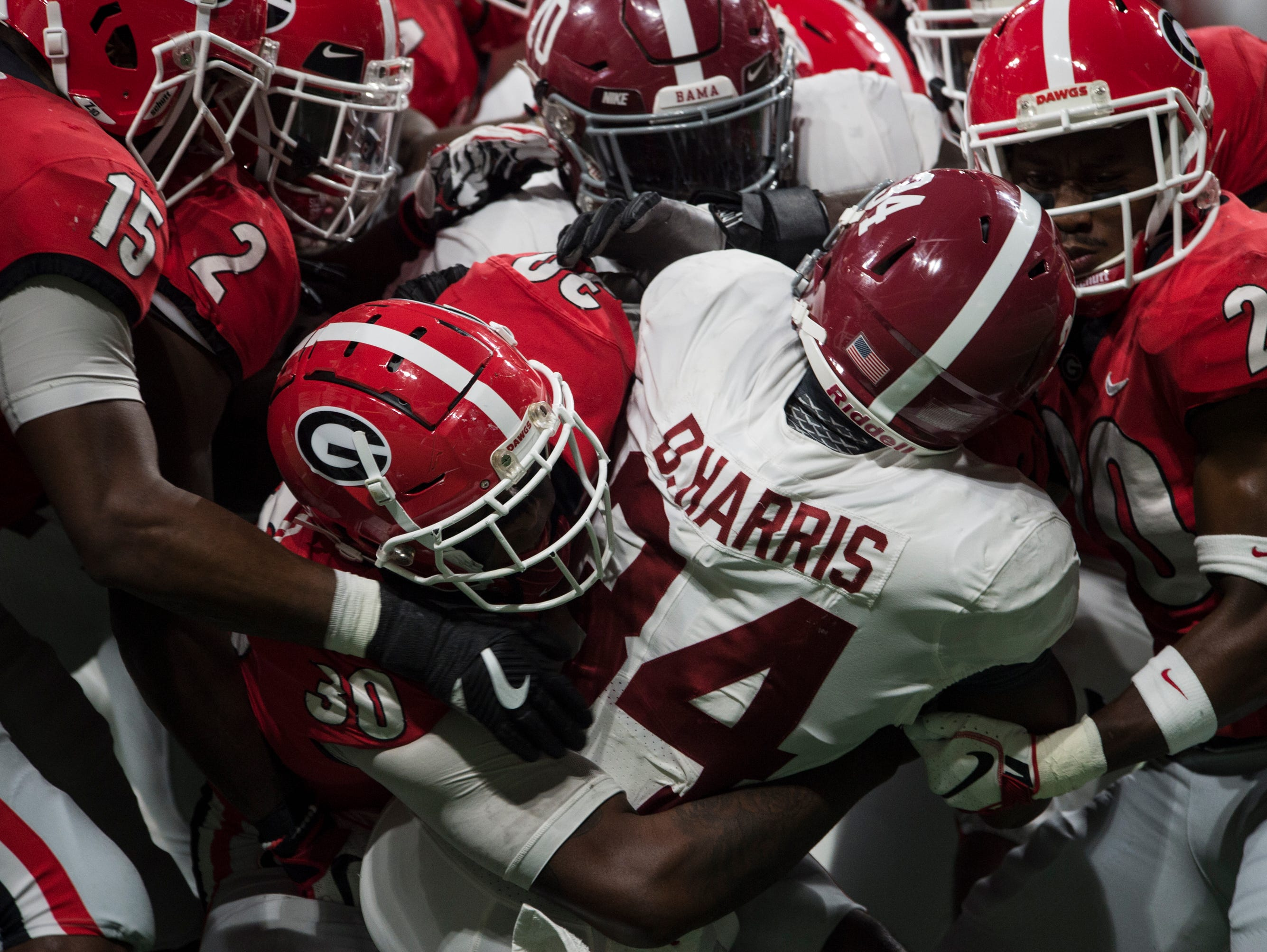 Alabama running back Damien Harris (34) is taken down by a swarm of Georgia defenders during the SEC Championship game at Mercedes-Benz Stadium in Atlanta, Ga., on Saturday Dec. 1, 2018. Georgia leads Alabama 21-14 at halftime.