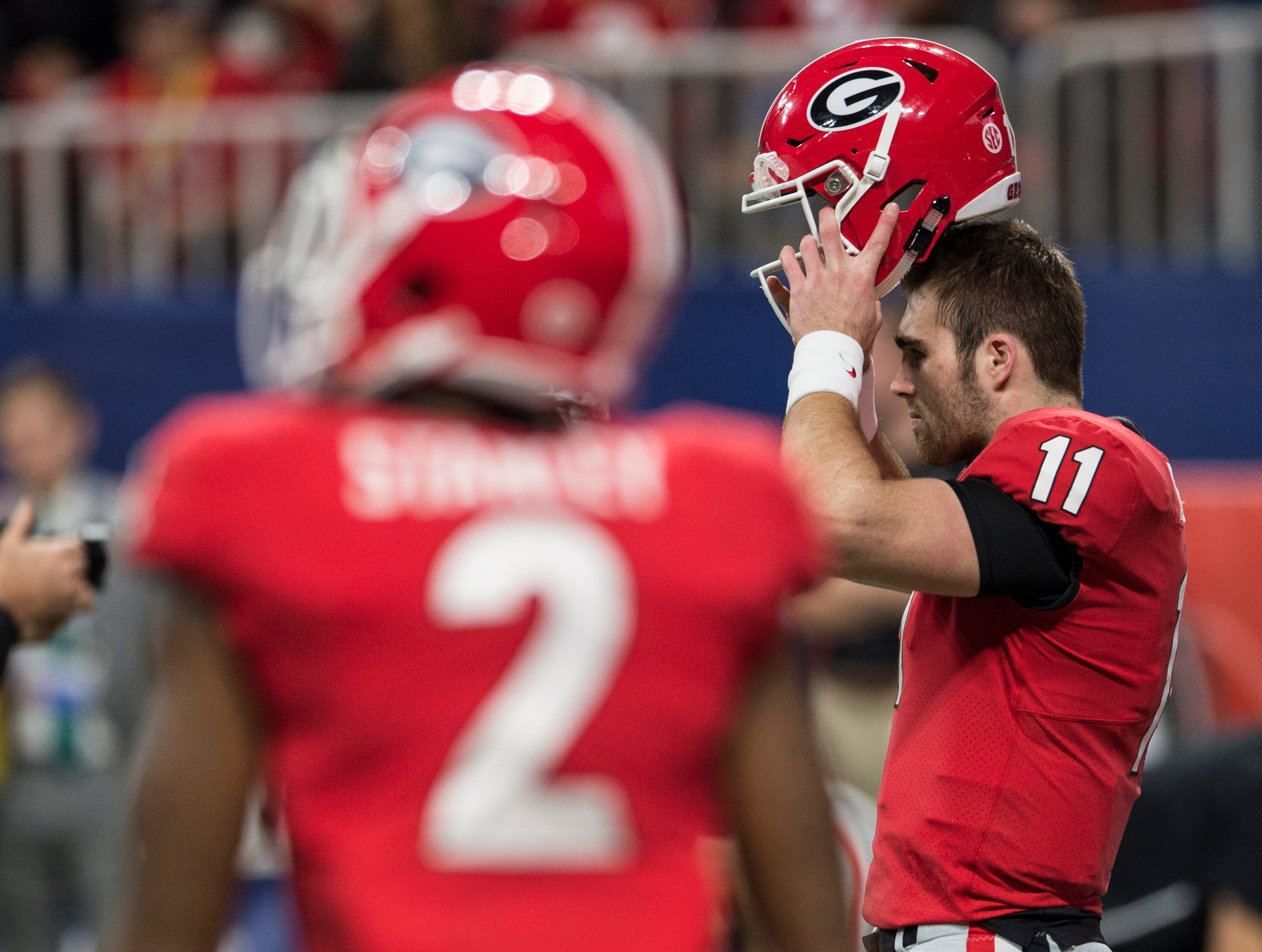 Georgia quarterback Jake Fromm (11) puts on his helmet during warm ups before the SEC Championship game at Mercedes-Benz Stadium in Atlanta, Ga., on Saturday Dec. 1, 2018.