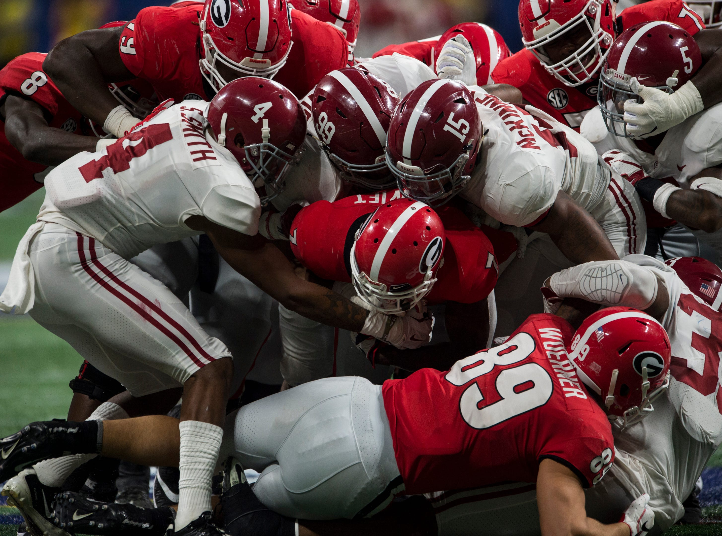 Georgia running back D'Andre Swift (7) is taken down by a swarm of Alabama defenders during the SEC Championship game at Mercedes-Benz Stadium in Atlanta, Ga., on Saturday Dec. 1, 2018. Georgia leads Alabama 21-14 at halftime.