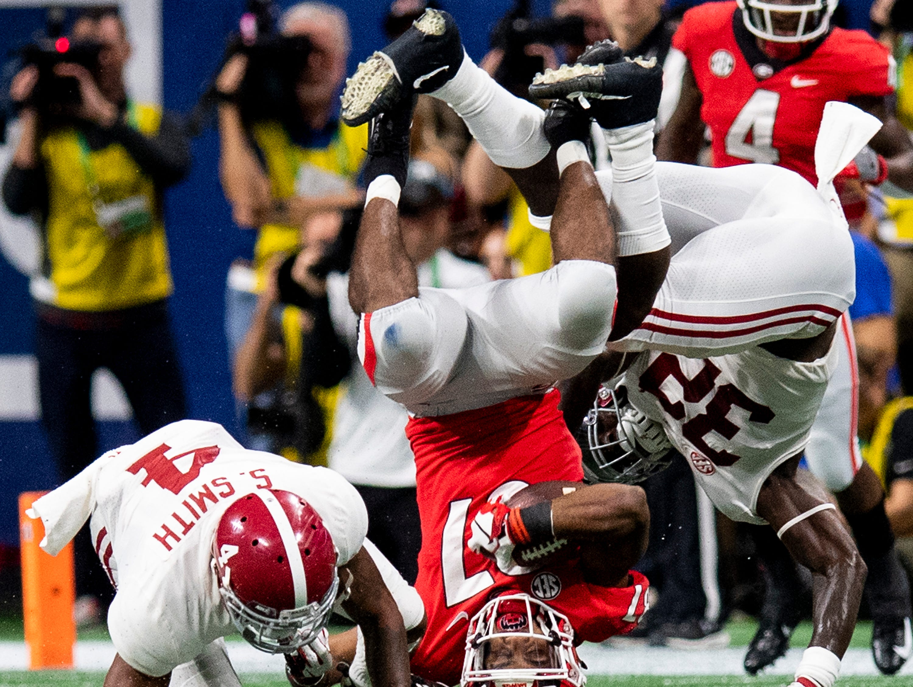 Alabama defensive back Saivion Smith (4) and linebacker Dylan Moses (32) upend Georgia wide receiver Tyler Simmons (87) during first half action of the SEC Championship Game at Mercedes Benz Stadium in Atlanta, Ga., on Saturday December 1, 2018.
