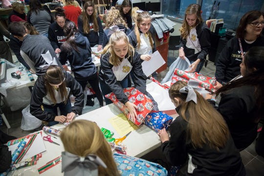 Hundreds of volunteers gather at Toyota of Muncie to wrap and deliver presents during the 2018 Secret Families Christmas Charity event. Three groups worked to buy the gifts, wrap them and deliver them.
