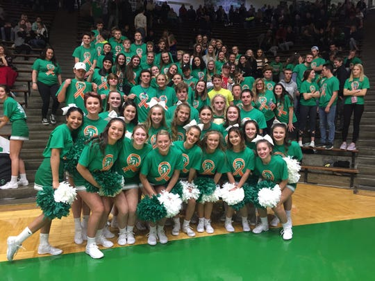 New Castle cheerleaders and student section wore custom shirts to support basketball coach Daniel Cox during the Trojans' game against Hamilton Heights.
