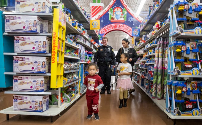 Kids and their officers wander through the toy aisles at the Cop-n-Kids Shopping Spree on Saturday at the Southside Walmart. The event was able to help provide 50 kids Christmas presents this year thanks to a grant through Walmart.
