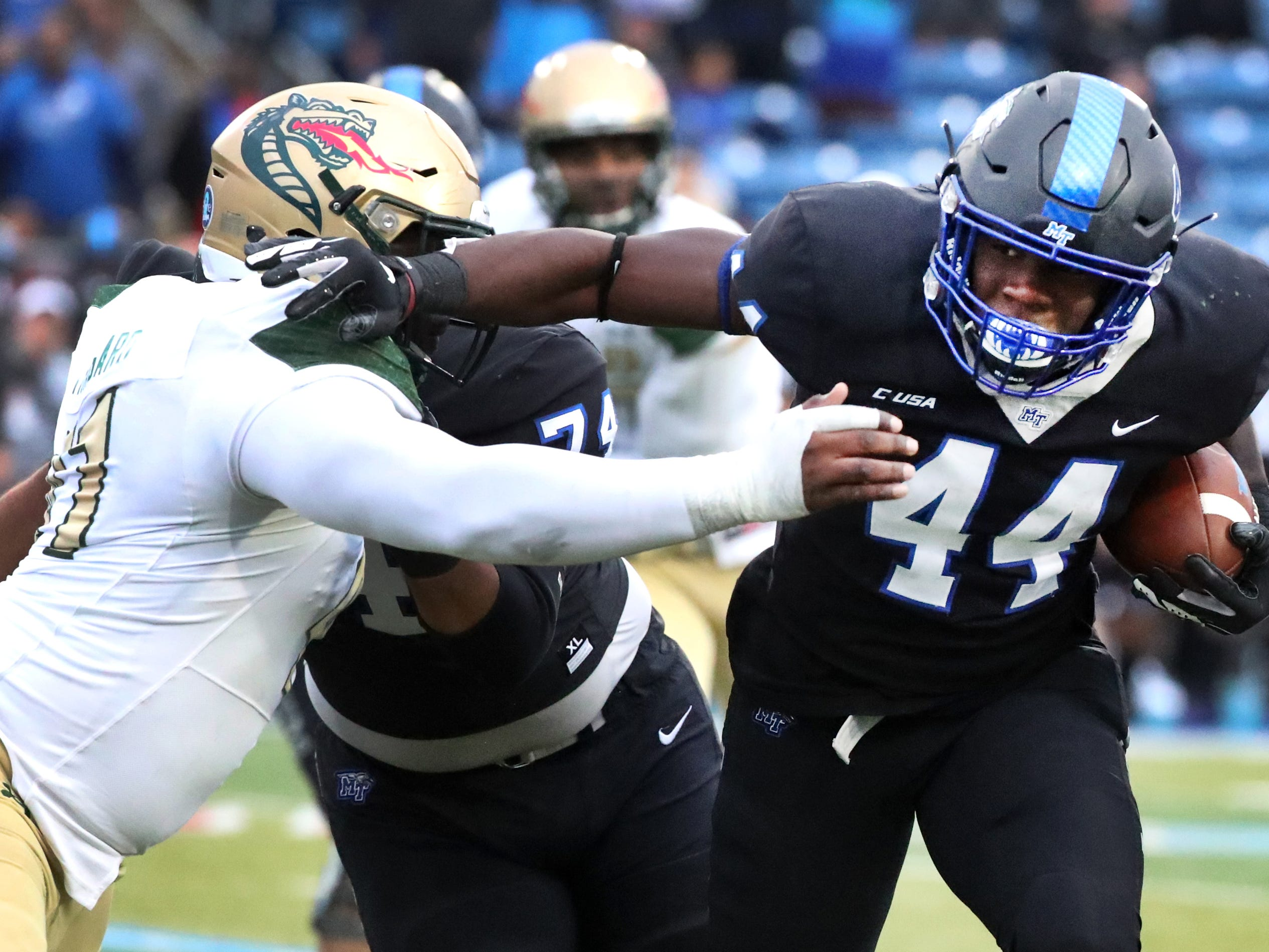 MTSU's running back Chaton Mobley (44) runs the ball as UAB's defensive lineman Quindarius Thagard (41) moves in for a tackle that Mobley shakes off during the Conference USA Championship at MTSU on Saturday, Dec. 1, 2018.