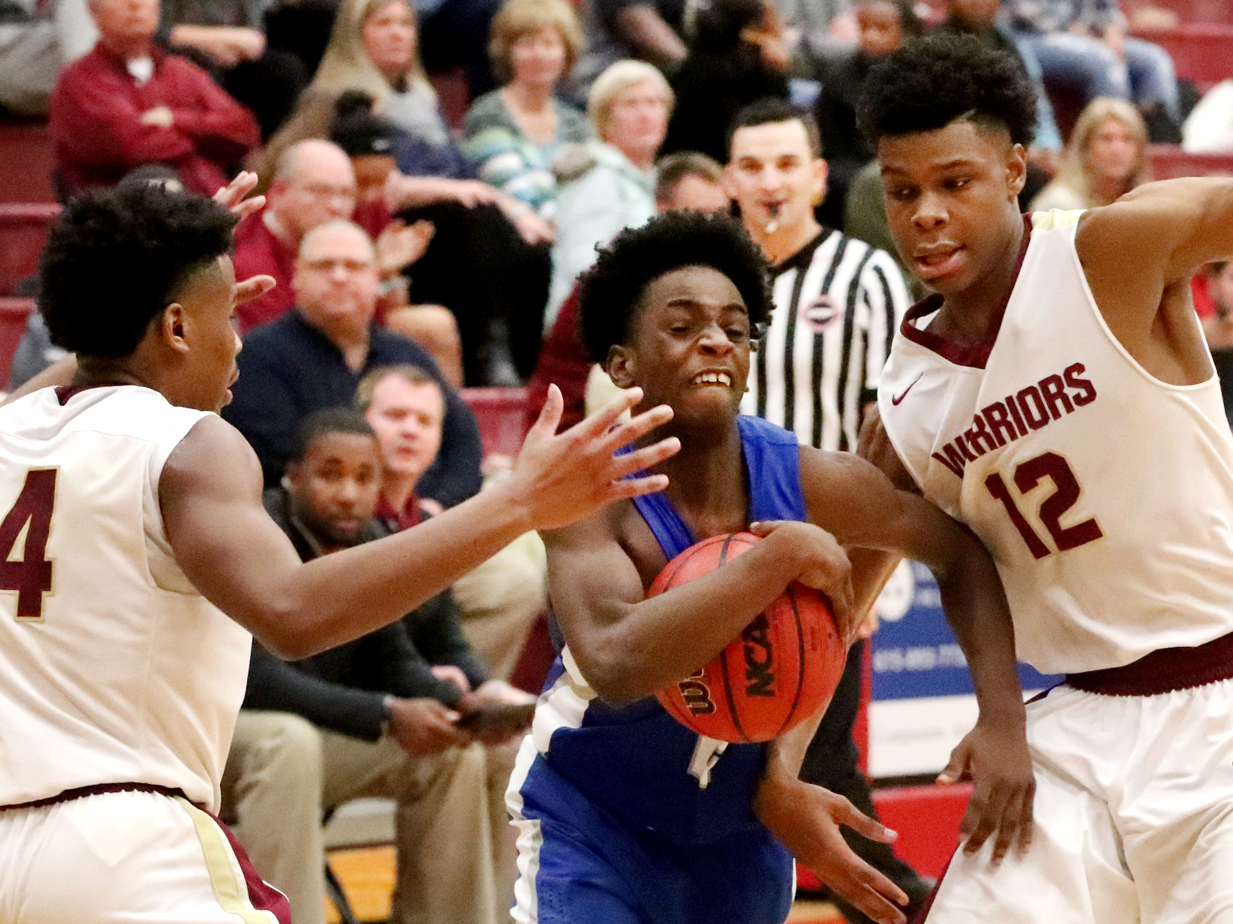 Lebanon's Malcolm Logue (2) pushes through RiverdaleÕs Deron Perry (14) and Elijah Cobb (12) to head to the basket during the game at Riverdale on Friday, Nov. 30, 2018.