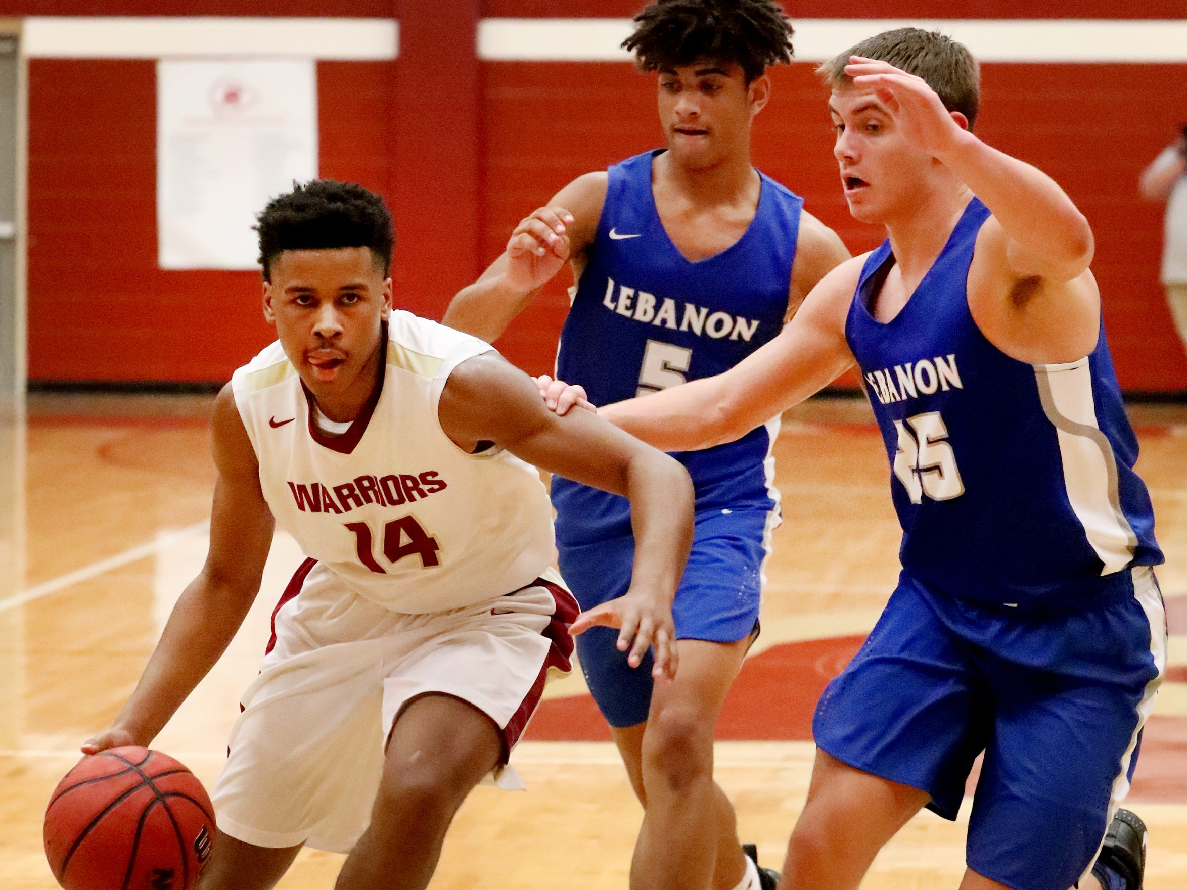 RiverdaleÕs Deron Perry (14) drives toward the basket as Lebanon's Jeremiah Hastings (5) and Lebanon's Ethan Njezic (25) cover him during the game at Riverdale on Friday, Nov. 30, 2018.