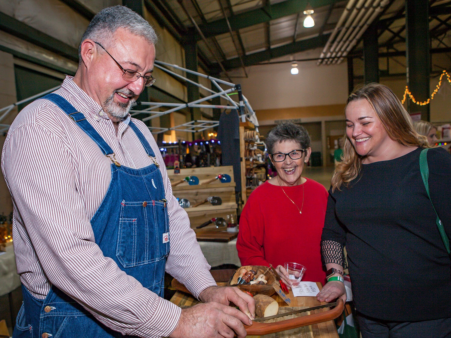 Steve Hopper demonstrates a cutting tool for Glenda Windrow and Rachelle Ayers at Mistletoe & Martinis, the preview party for Junior League of Murfreesboro's 2018 Hollyday Marketplace.