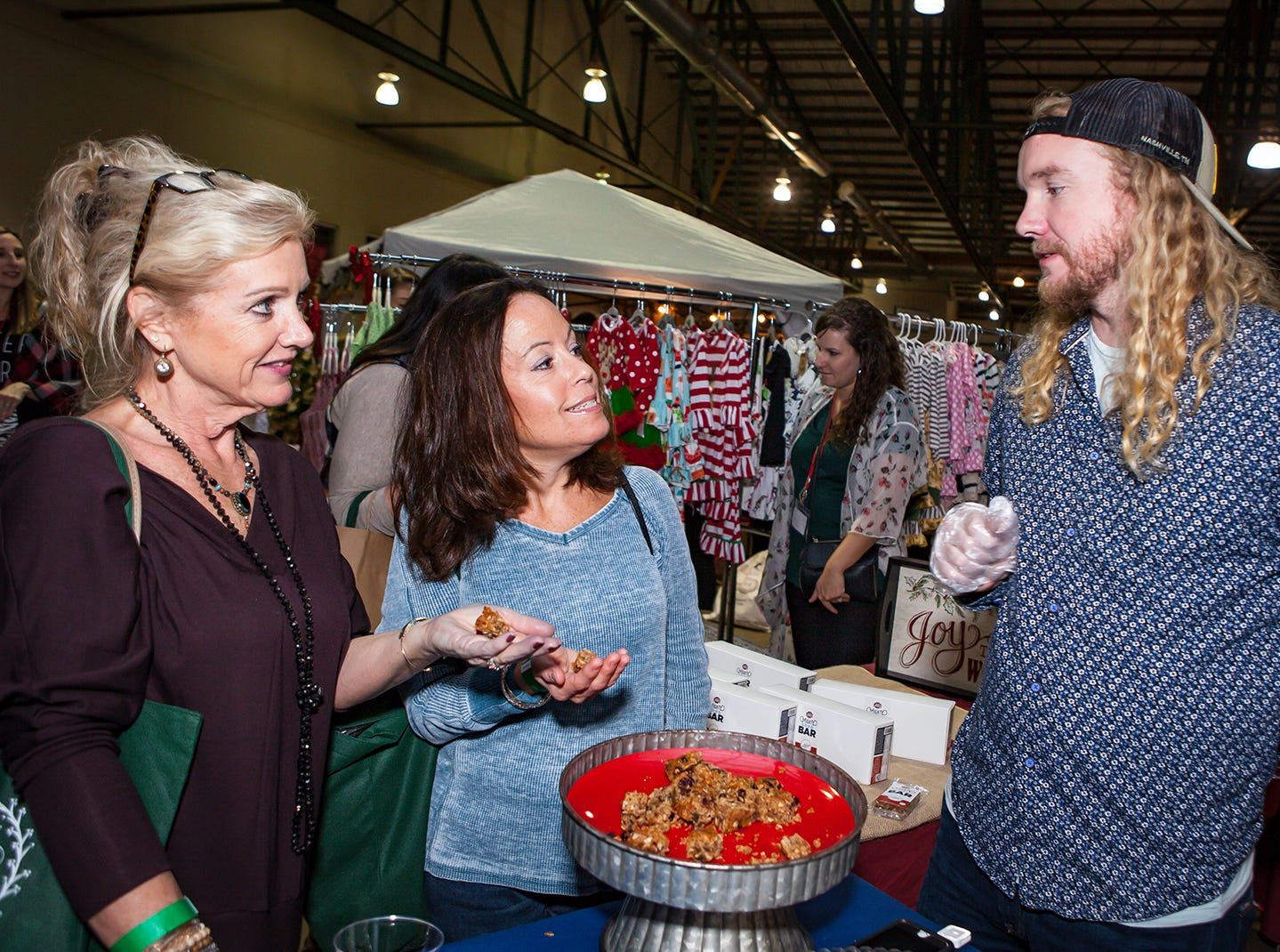Alesia Normand and Ronya Cervantez sample a treat from Jake Burman at MIstletoe & Martinis on Friday, Nov. 30, the preview party for the 2018 Hollyday Marketplace hosted by the Junior League of Murfreesboro.