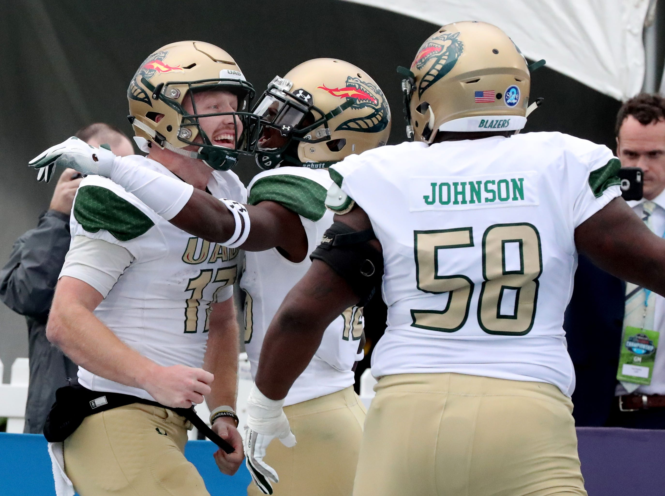 UAB's quarterback Tyler Johnston III (17) celebrates his touchdown with wide receiver Kendall Parham (16) and offensive lineman Malique Johnson (58) during the Conference USA Championship at MTSU on Saturday, Dec. 1, 2018, against MTSU.