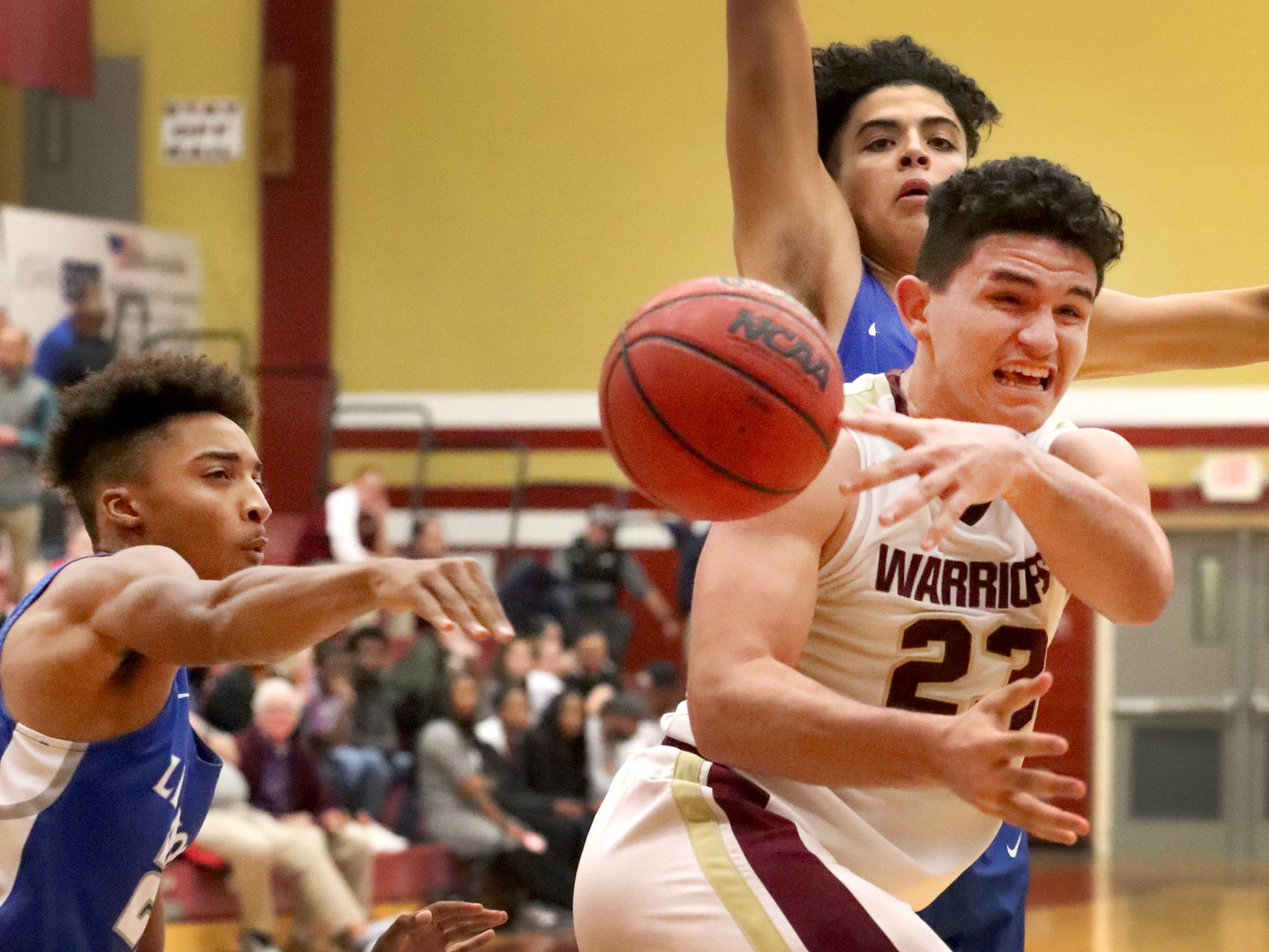 RiverdaleÕs Maliek McAllister (23) passes the ball under the basket as Lebanon's Polo Phillips (22) and Jackson Stafford (23) guards him during the game at Riverdale on Friday, Nov. 30, 2018.