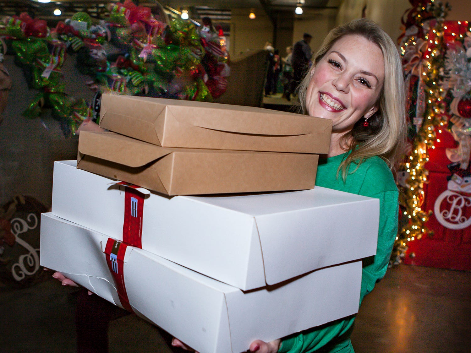 April Hoke carries boxes of treats at Mistletoe & Martinis on Friday, Nov. 30, the preview party for the 2018 Hollyday Marketplace hosted by the Junior League of Murfreesboro.