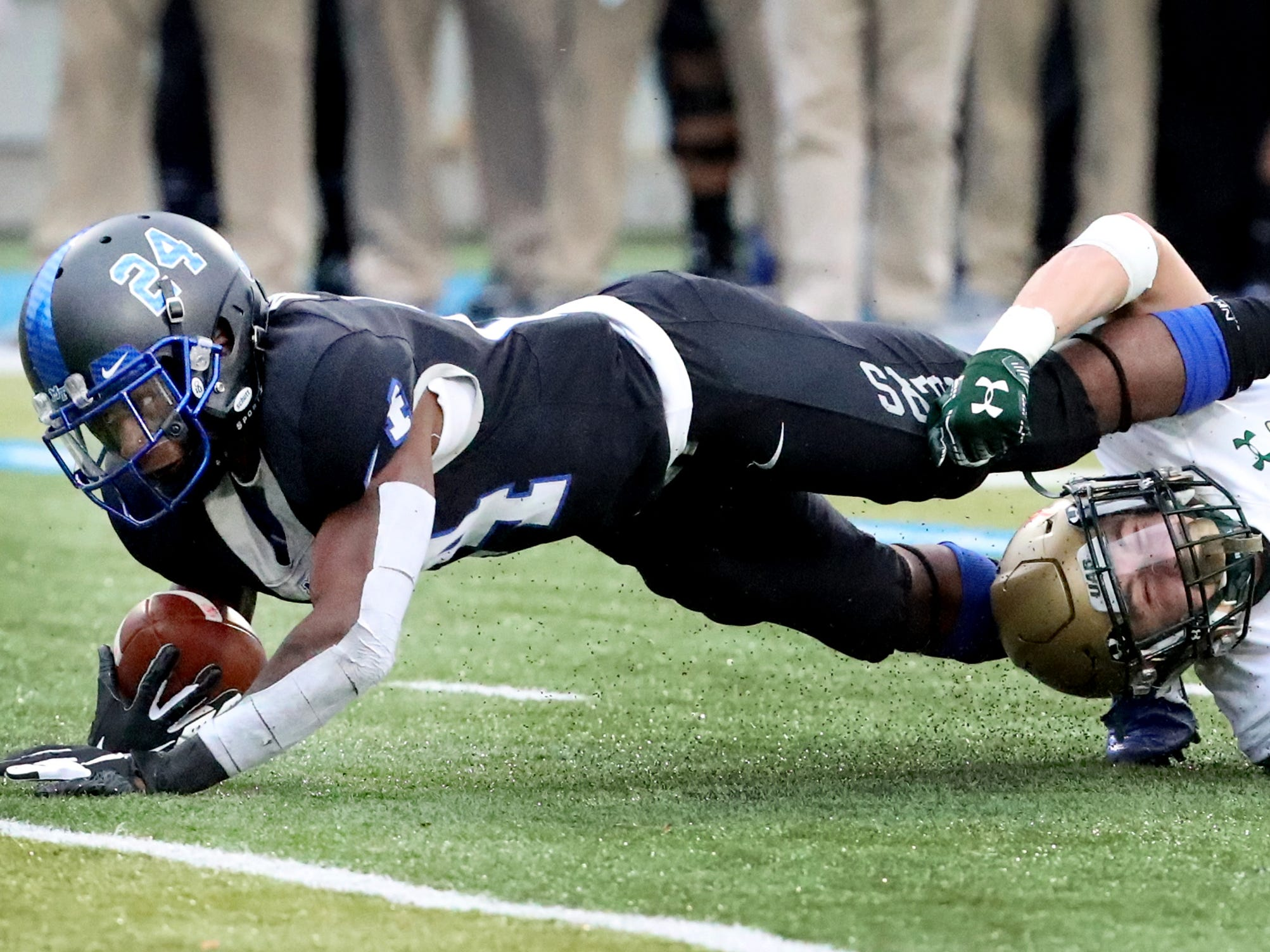 MTSU's wide receiver Zack Dobson (24) runs the ball as he is stopped by UAB's linebacker Kristopher Moll (20) during the Conference USA Championship at MTSU on Saturday, Dec. 1, 2018.