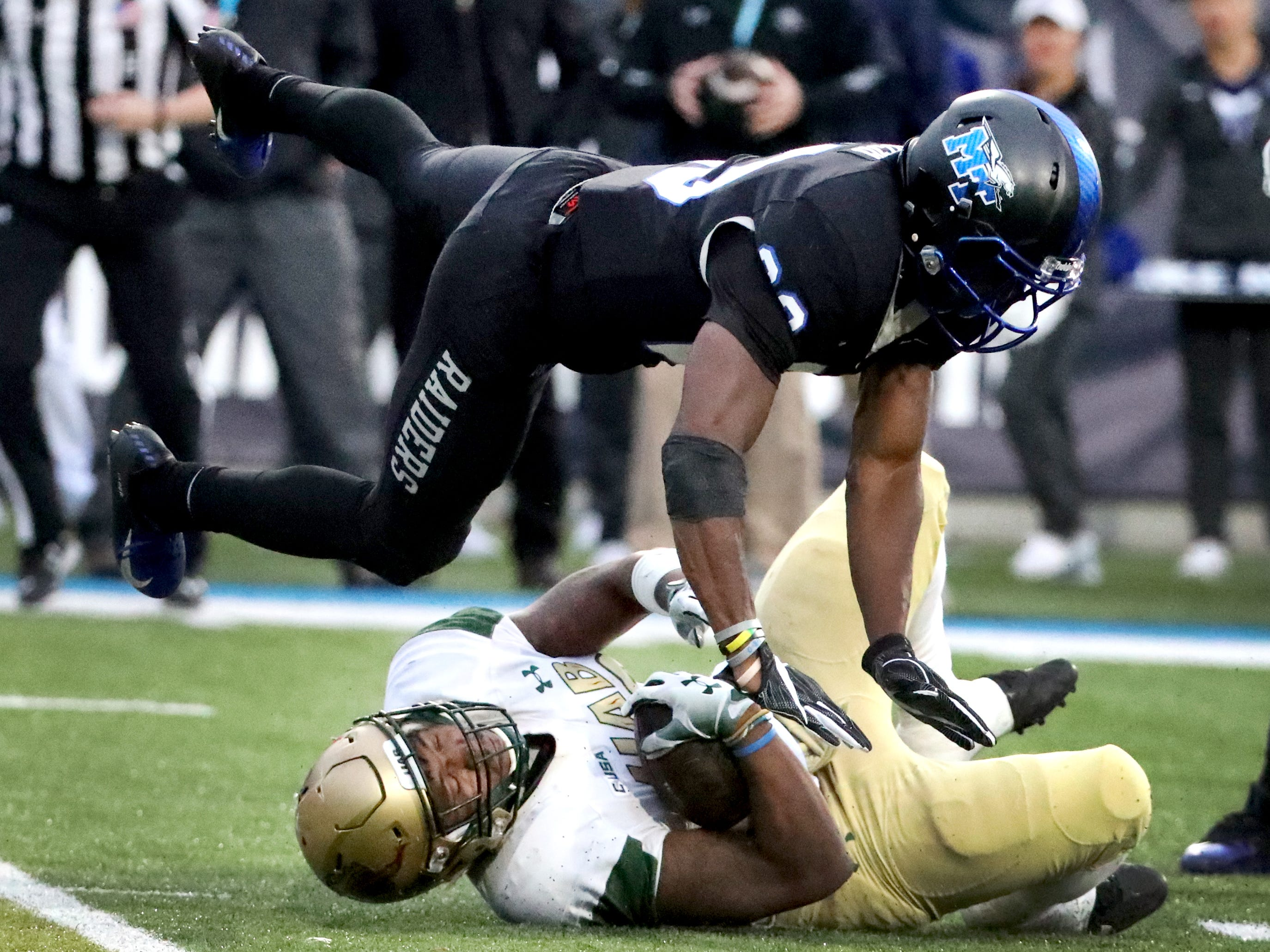 UAB's linebacker Kristopher Moll (20) crashes into MTSU's defensive back Wesley Bush (23) after safety Reed Blankenship (12) brings down Moll during the Conference USA Championship at MTSU on Saturday, Dec. 1, 2018.