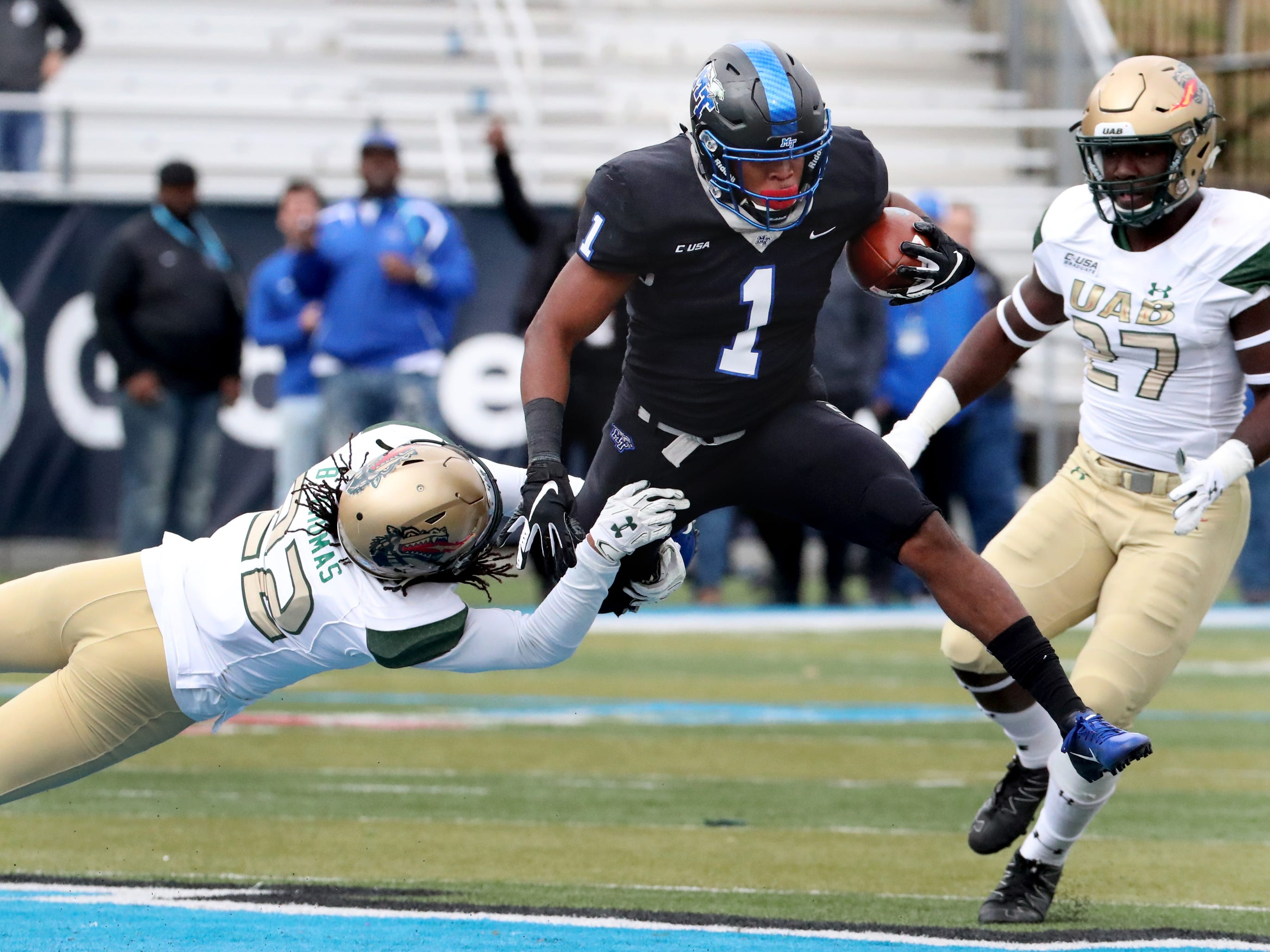 MTSU's running back Terelle West (1) runs the ball as he shakes off a tackled by UAB's safety Broderick Thomas (22) during the Conference USA Championship at MTSU on Saturday, Dec. 1, 2018.