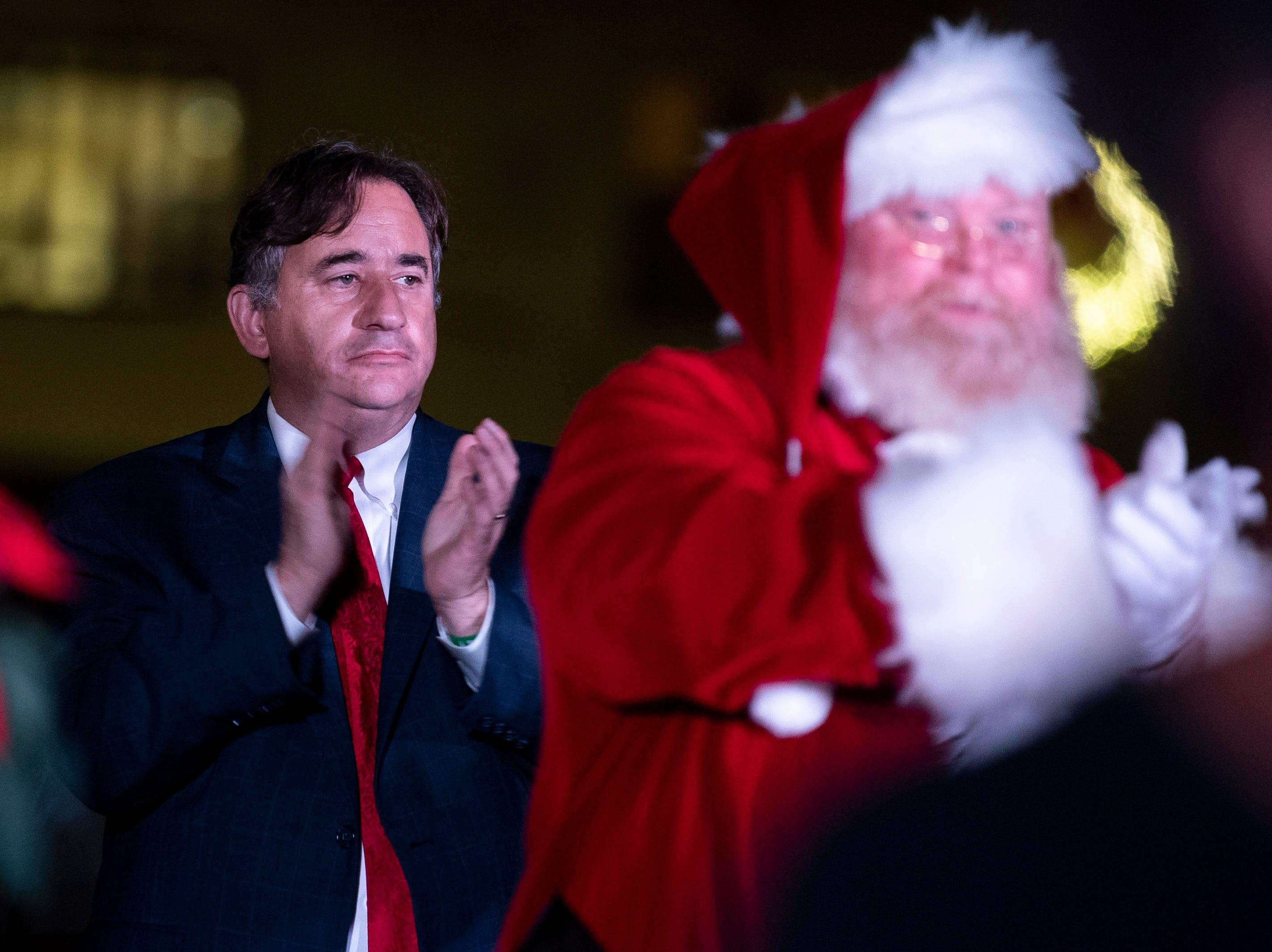 Nashville Vice Mayor Jim Shulman, left, claps along to the The Lake Providence Missionary Baptist Church Choir with Santa Claus, right, during the Metro Nashville Christmas Tree Lighting event at Public Square Park in Nashville, Tenn., Friday, Nov. 30, 2018.