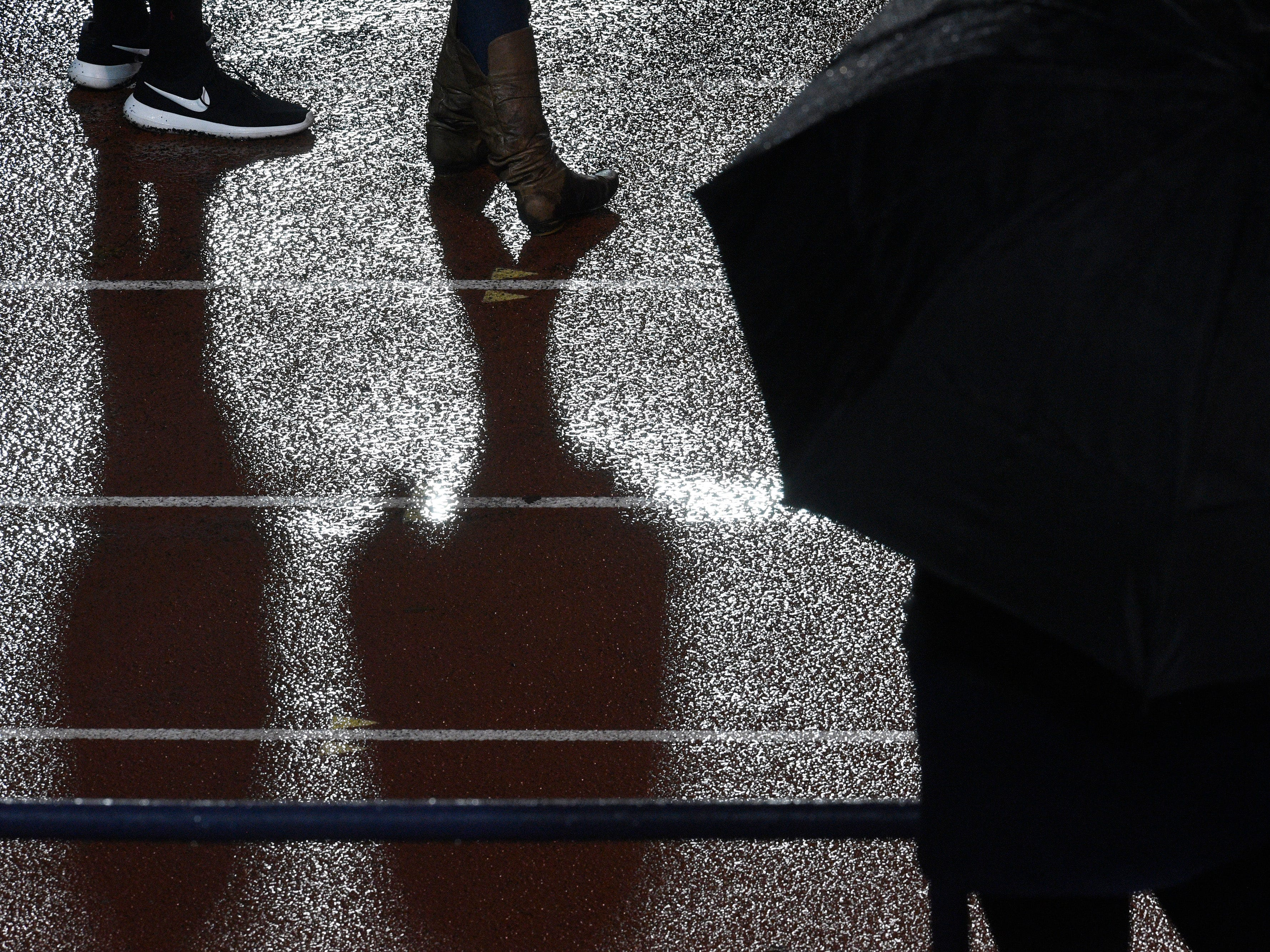 Fans are reflected on the wet track at the Division II-AAA BlueCross Bowl state championship at Tennessee Tech's Tucker Stadium in Cookeville, Tenn., on Friday, Nov. 30, 2018.