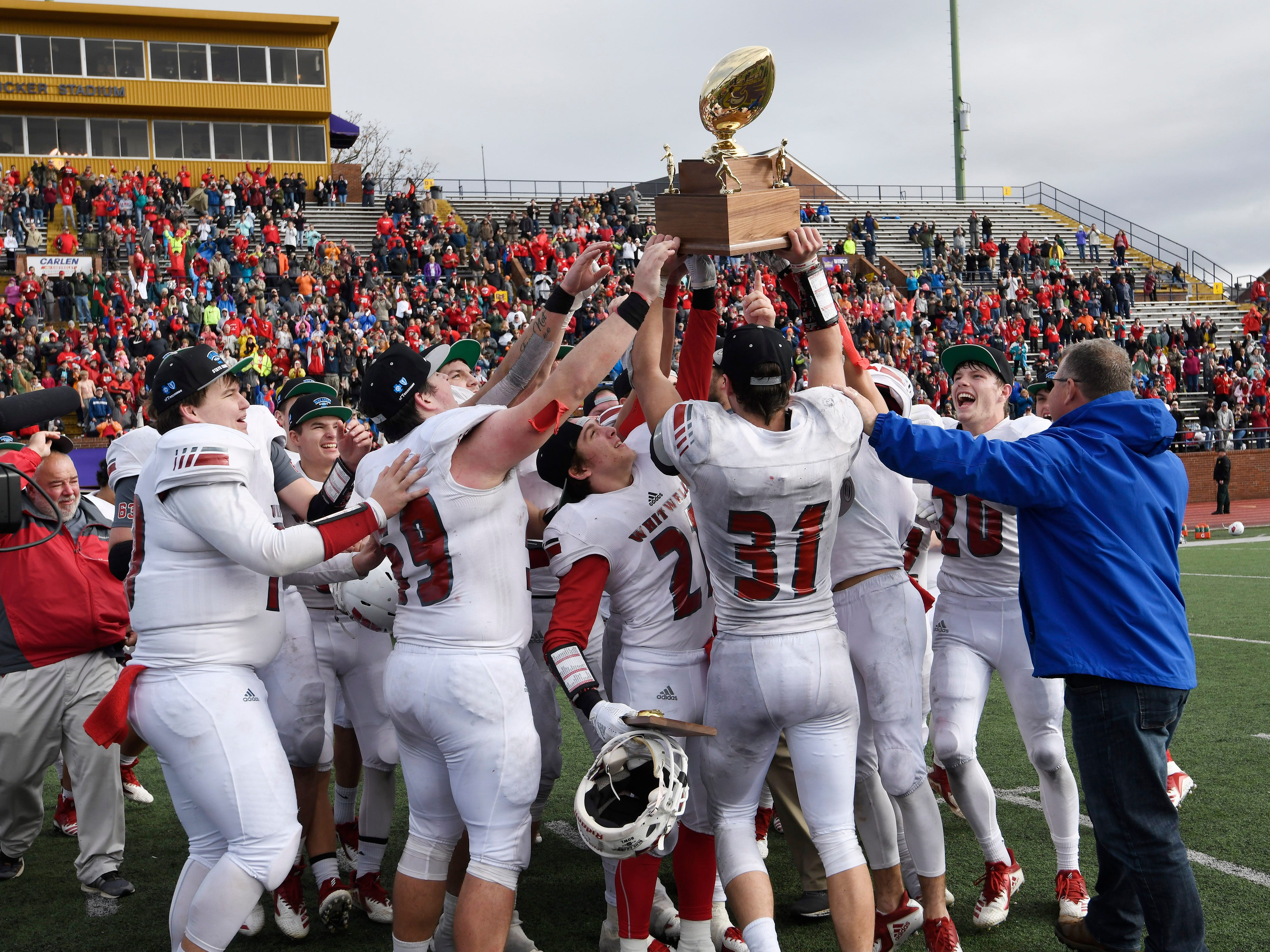 Whitwell players celebrate with the championship trophy at the Class I-A BlueCross Bowl state championship at Tennessee Tech's Tucker Stadium in Cookeville, Tenn., on Saturday, Dec. 1, 2018.