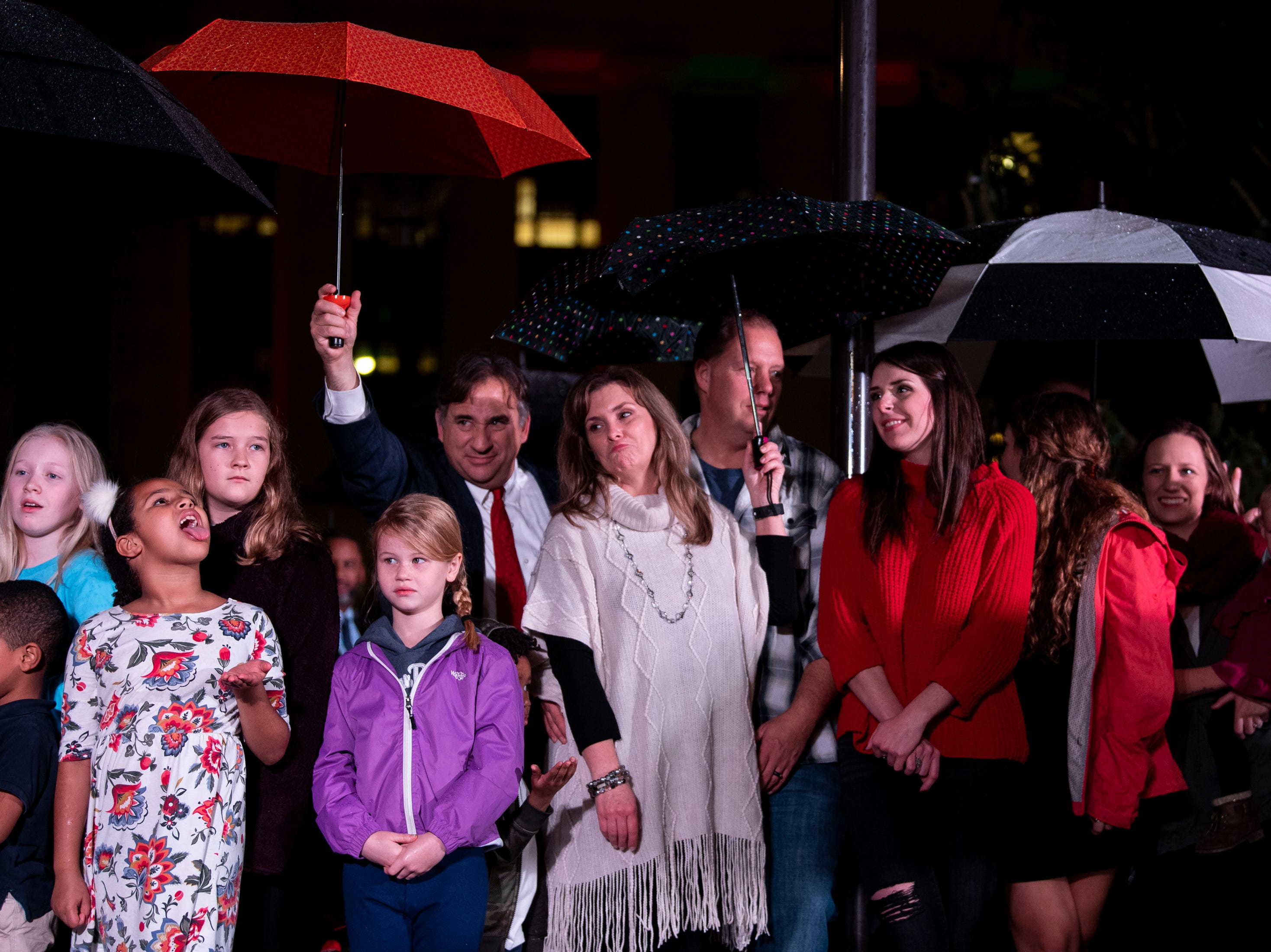 Guests take cover from rain during the Metro Nashville Christmas Tree Lighting event at Public Square Park in Nashville, Tenn., Friday, Nov. 30, 2018.