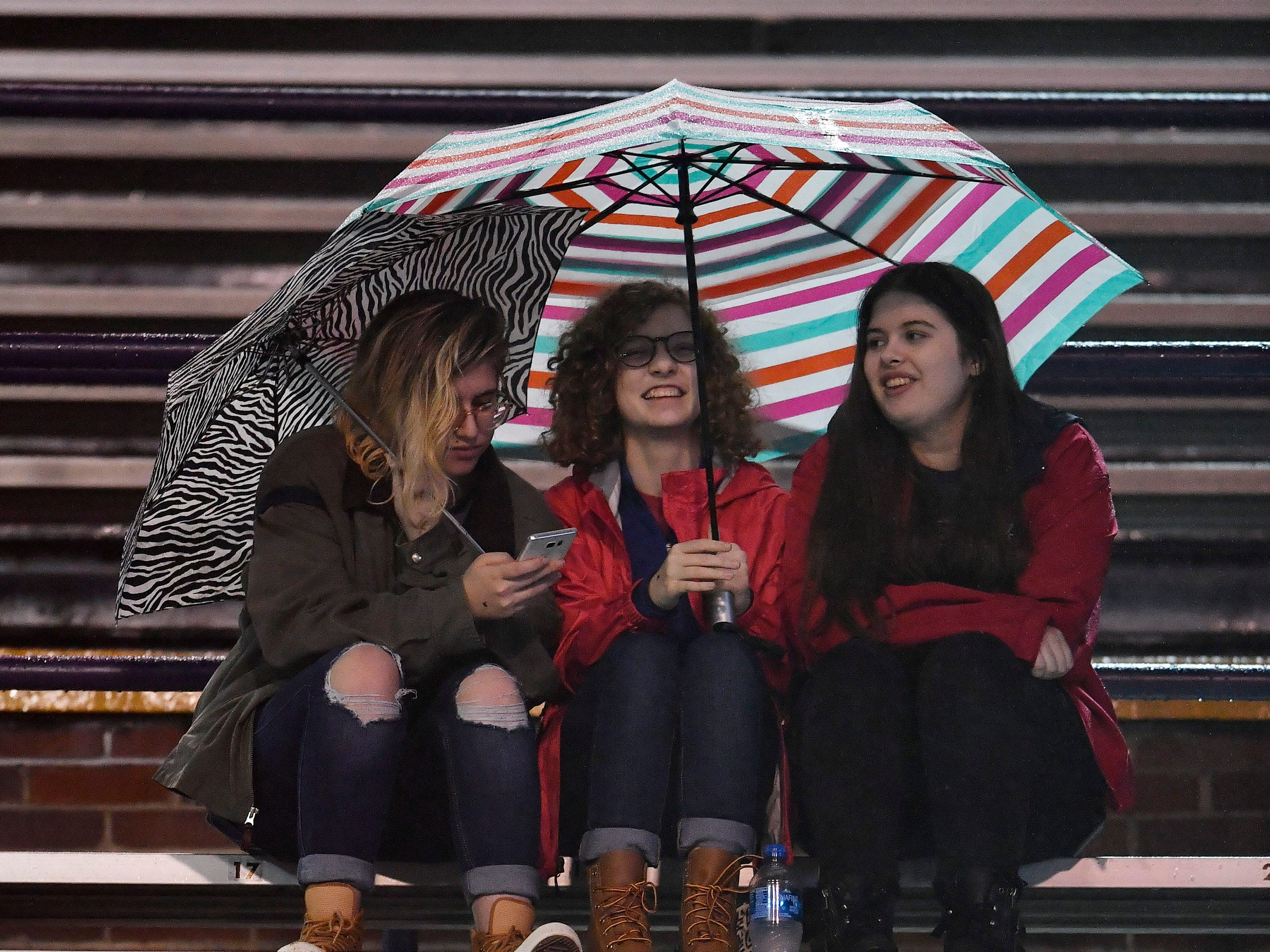 BA fans huddle under an umbrella in the second half at the Division II-AAA BlueCross Bowl state championship at Tennessee Tech's Tucker Stadium in Cookeville, Tenn., on Friday, Nov. 30, 2018.