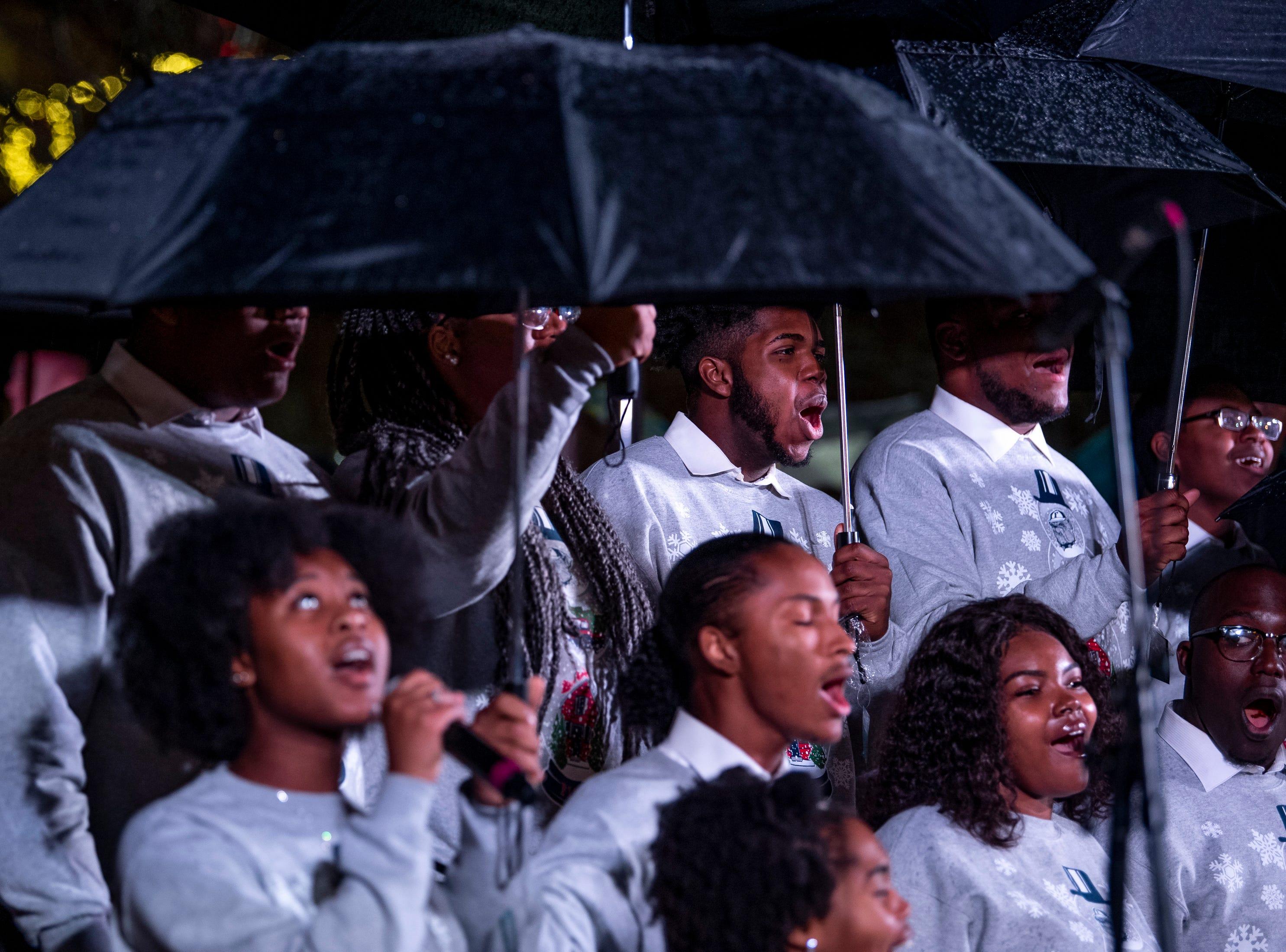 The Fisk Jubilee Singers perform as rain falls during the Metro Nashville Christmas Tree Lighting event at Public Square Park in Nashville, Tenn., Friday, Nov. 30, 2018.