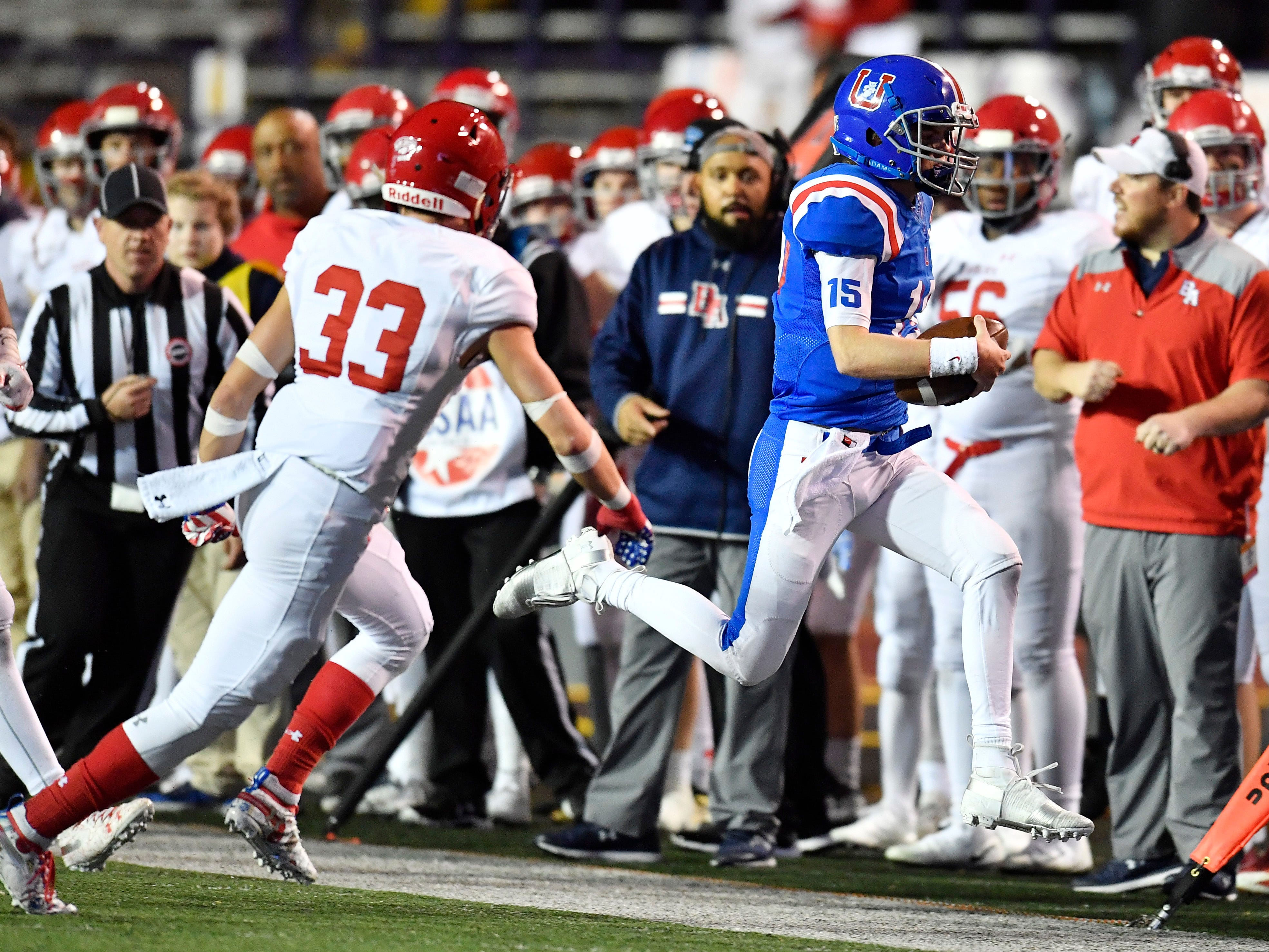 Memphis Univ. School quarterback Sellers Shy (15) scrambles out of bounds for a first down defended by Brentwood Academy defensive back Aaron Lovins (33) in the e first quarter at the Division II-AAA BlueCross Bowl state championship at Tennessee Tech's Tucker Stadium in Cookeville, Tenn., on Friday, Nov. 30, 2018.