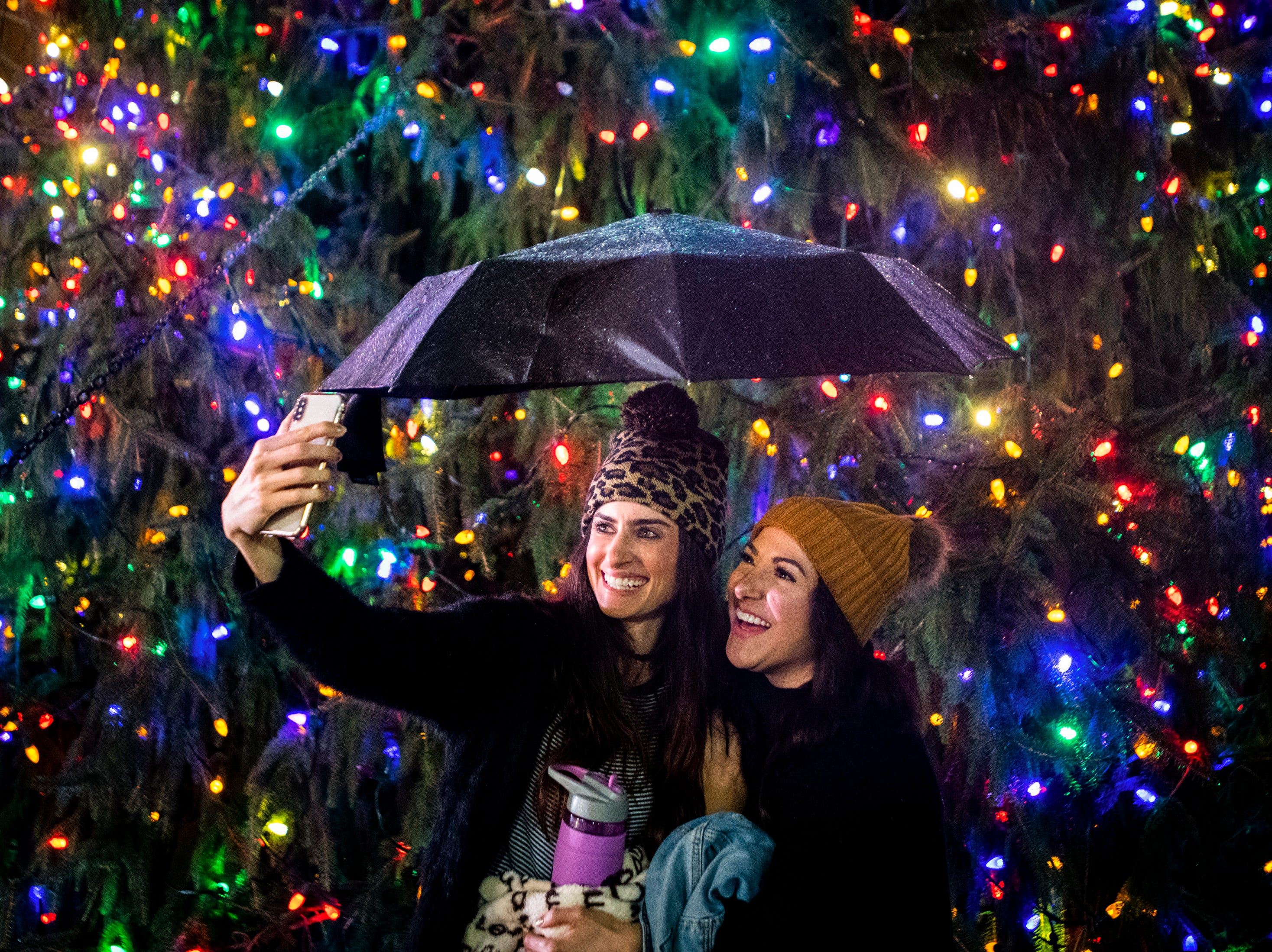Ashley Scovil, left, and Grethel Icabalceta, right, both of Nashville, take a picture in front of the tree during the Metro Nashville Christmas Tree Lighting event at Public Square Park in Nashville, Tenn., Friday, Nov. 30, 2018.