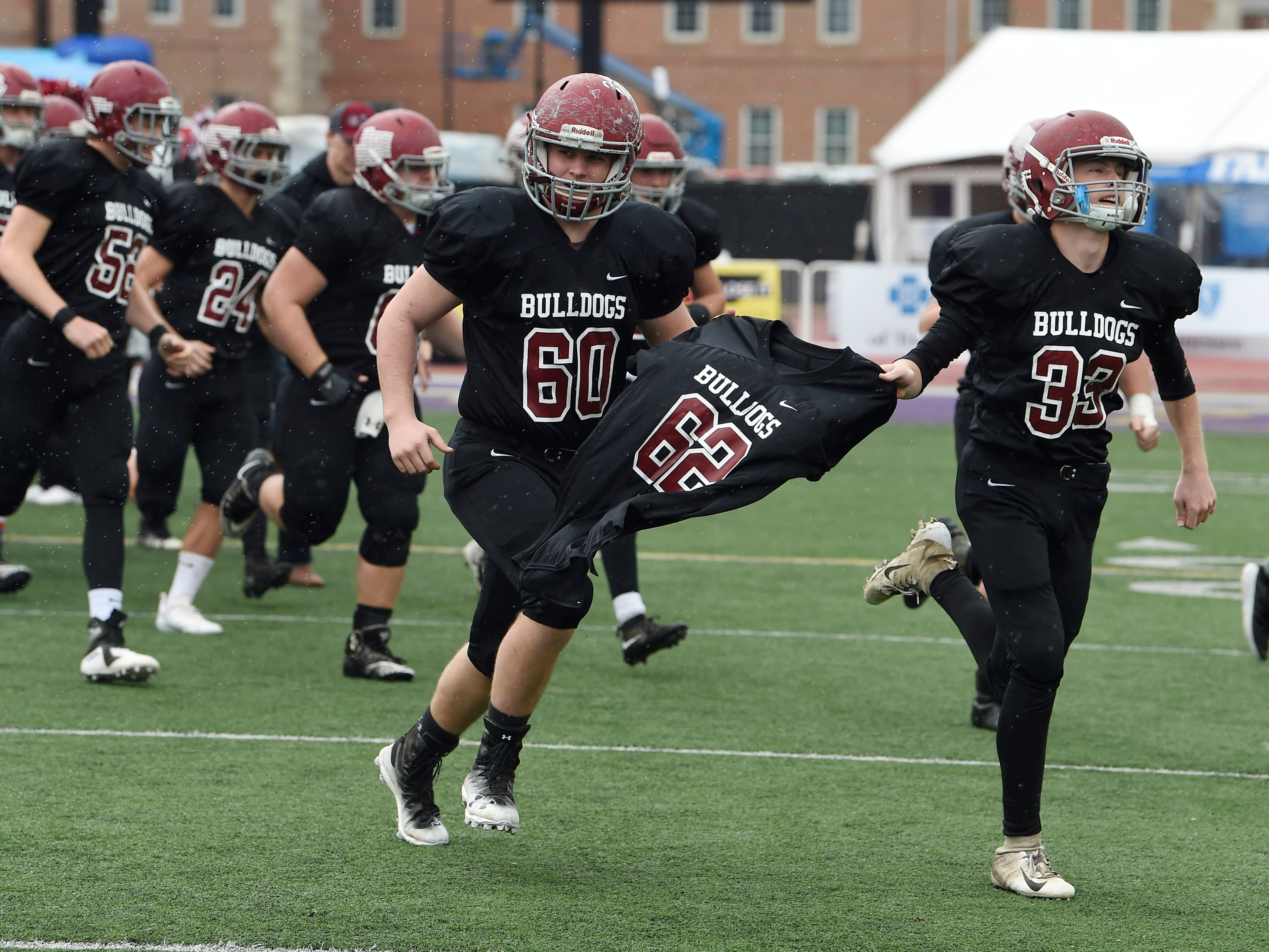 Cornersville players carry the jersey of former player Bryan Giles (62) onto the field for the start of the Class I-A BlueCross Bowl state championship at Tennessee Tech's Tucker Stadium in Cookeville, Tenn., on Saturday, Dec. 1, 2018. Bryan Giles died in June 2017