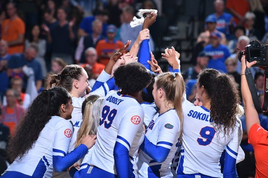 The Florida Gators volleyball team celebrates after sweeping FGCU, 3-0, in the second round of the NCAA tournament in Orlando on Friday.