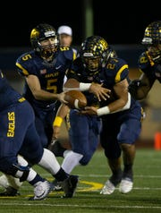 Naples quarterback Drew Wiltsie hands the ball off to running back Chez Mellusi during their game against Miami Northwestern on Friday at  Staver Field.