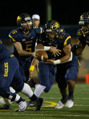 Naples quarterback Drew Wiltsie hands the ball off to running back Cesare Mellusi during their game against Miami Northwestern, Friday, Nov. 30, 2018 at Naples' Staver Field.