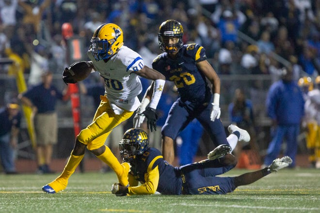 Miami-Northwestern Romello Brinson breaks a tackle by Naples' D'Andre St. Jean to score a touchdown Friday at Staver Field.