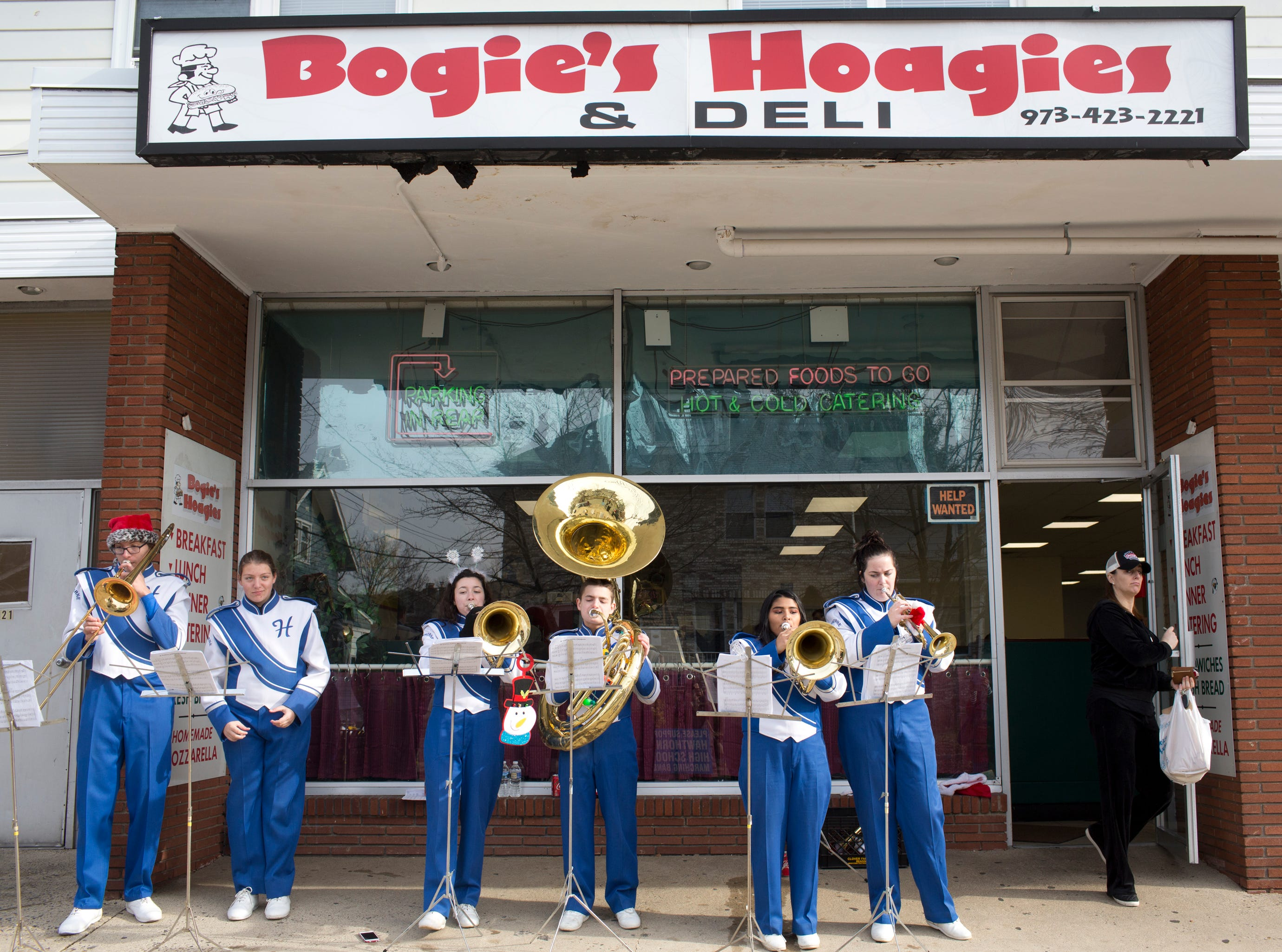 (From left) Daniel Sokolski, Meadow Ciccarella, Heather Scott, T.J. Marks, Maria Angeles and Paige Grenier with the Hawthorne High School Marching Band play some more holiday music outside of Bogie's Hoagies and Deli after the 33rd Annual Santa Parade in Hawthorne on Saturday, Dec. 1, 2018.